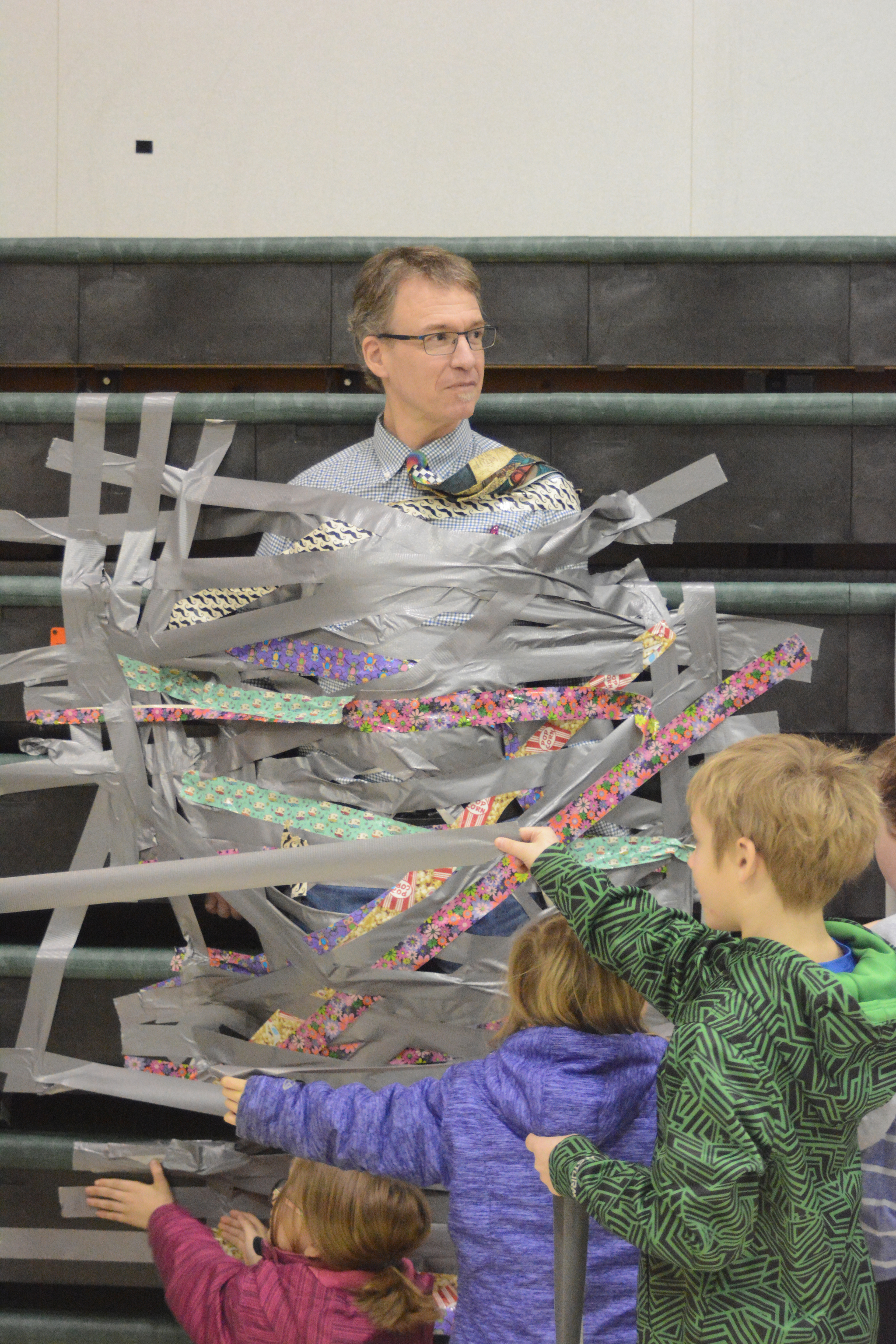 West Homer Elementary Principal Eric Waltenbaugh gets duct taped to the wall in the multipurpose room. Students at West Homer and Fireweed Academy got the reward of plastering duct tape across the principals for filling up a jar with tokens handed out when a student showed good behavior like being respectful and responsible.