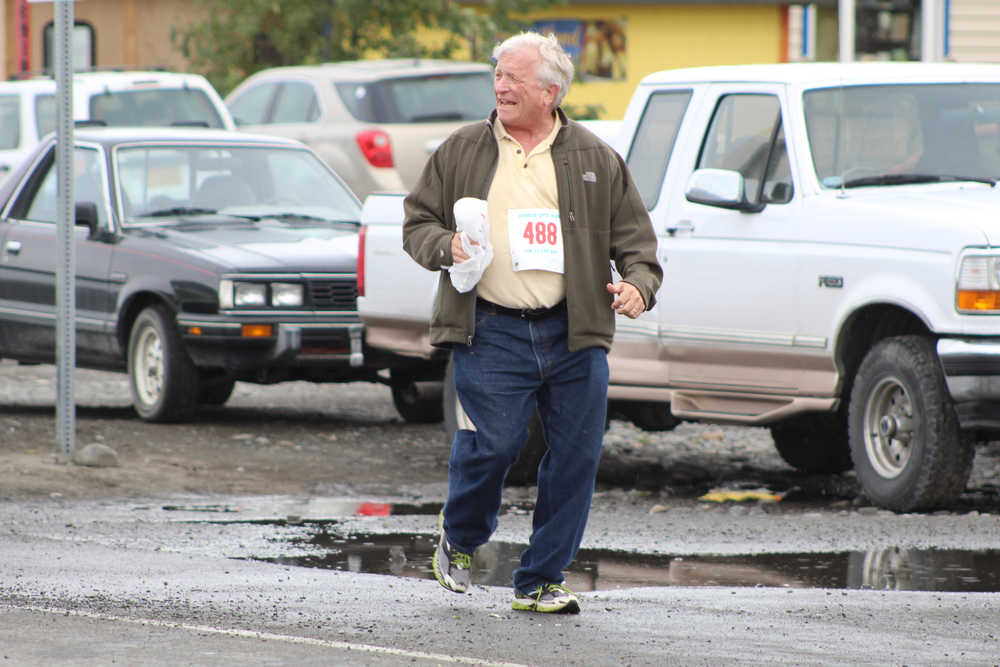 Robert Letson, 68, of Anchor Point laughs as acquintances cheer him on from across the street on the Spit. Letson finished 45th out of 49 in the walkers division of the Saturday, June 25 Spit Run with a time of 1:55:09.64.