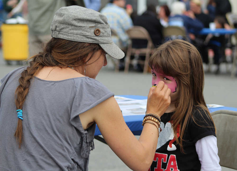 Brandi Scott paints four-year-old Erica Koch's face during the South Peninsula Hospital 60th Anniversary Party on Saturday, July 9.