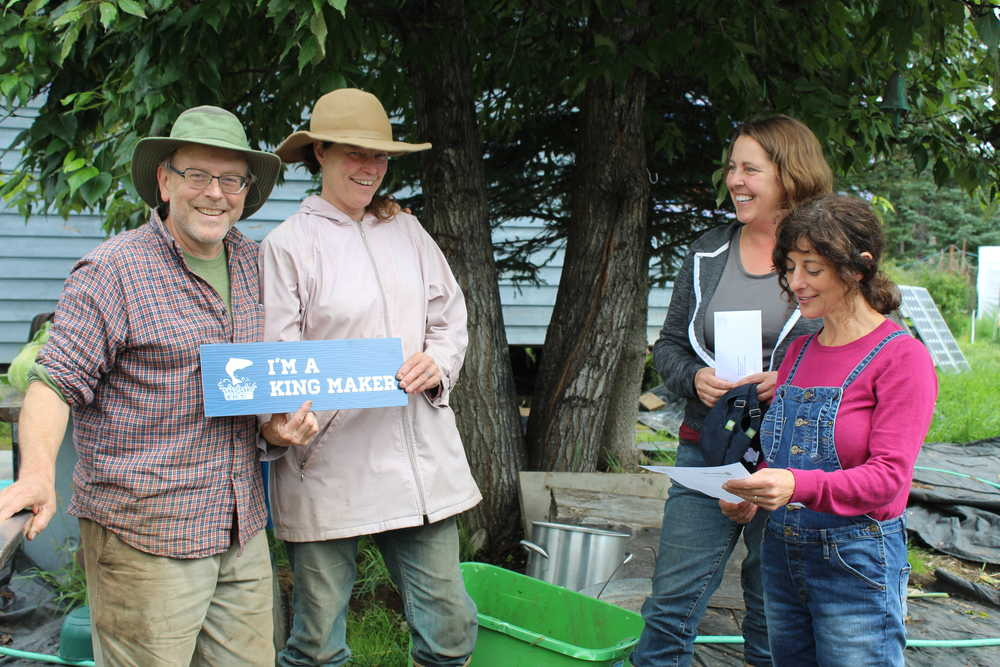Paul and Jen Castellani smile as Denise Jantz of Kachemak Heritage Land Trust and Coowe Walker of Kachemak Bay Research Reserve present them with the King Maker award for their care for their land, which has a stream with baby salmon in it. Walker reads a letter from KHLT explaining why the Castellanis are deserving of the King Maker award.