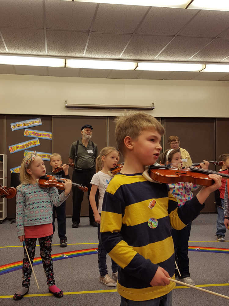 Violinists Gabe Stanislaw, Isabella Arno, Tatum Kirtly, Sawyer Shelby practice during class as Rep. Paul Seaton and Linda Reinhart look on.