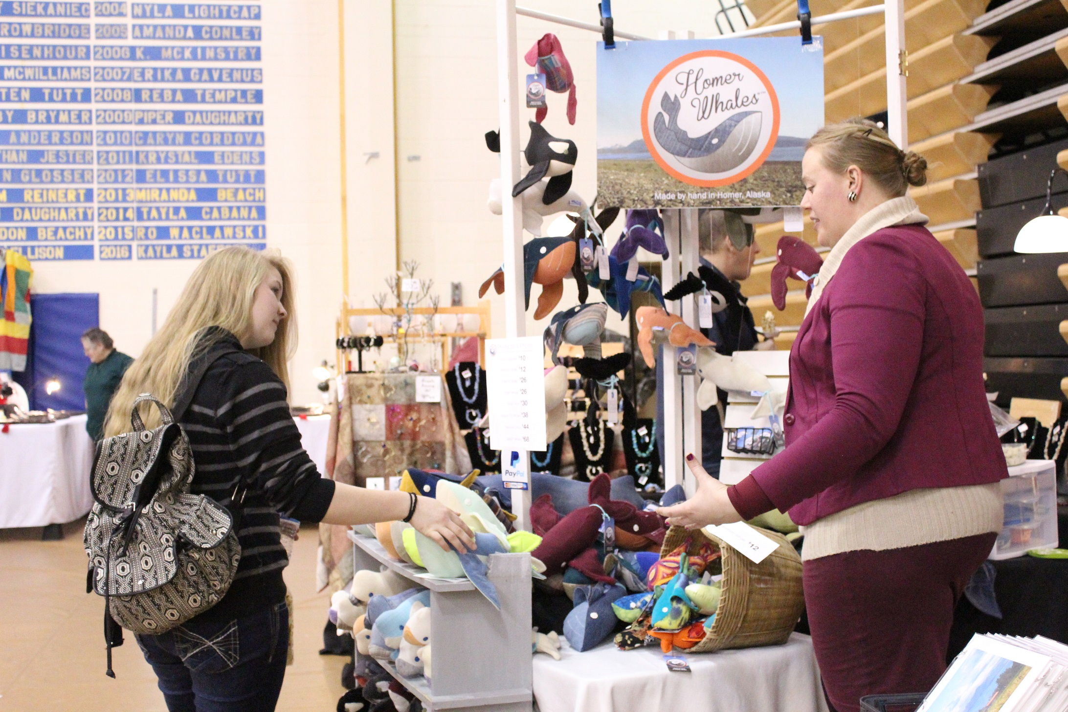 Abagail Kokai talks to a customer about her stuffed denim Homer Whales at the Nutcracker Faire on Saturday, Dec. 3.-Photo by Anna Frost, Homer News