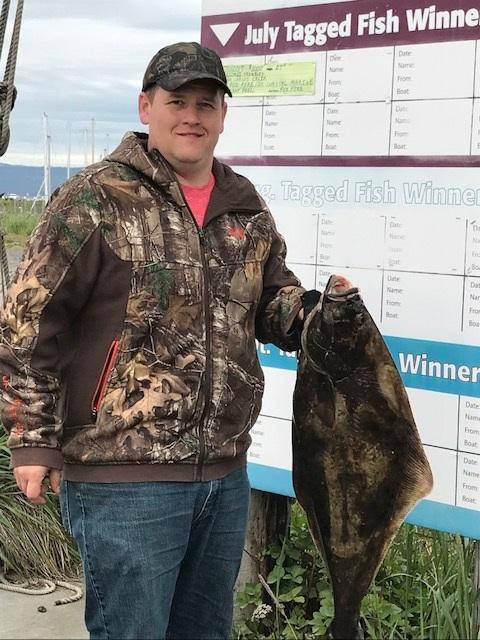 Jasen VanMieuwenhover of Wisconsin holds a left-hand halibut he caught fishing July 11 with Homer Ocean Charters, who also sold him his derby ticket. The $100 prize for a lefty was sponsored by Timer Bay B&B.