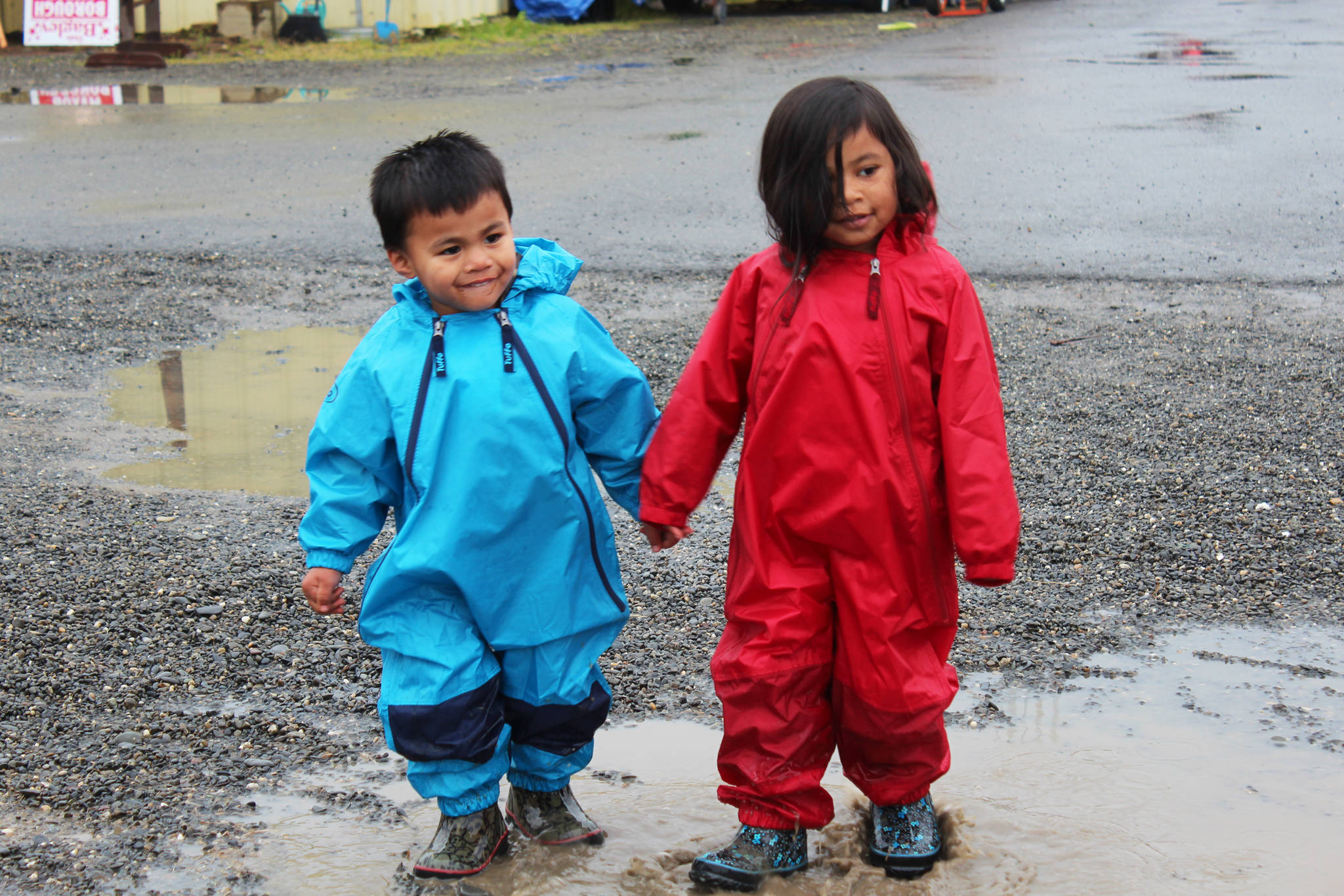 Siblings Everett Malone, 3, and Kaydence Malone, 4, splash around in the puddles spotting the fairgrounds during this year's Kenai Peninsula Fair on Friday, Aug. 18, 2017 in Ninilchik, Alaska. (Photo by Megan Pacer/Homer News)
