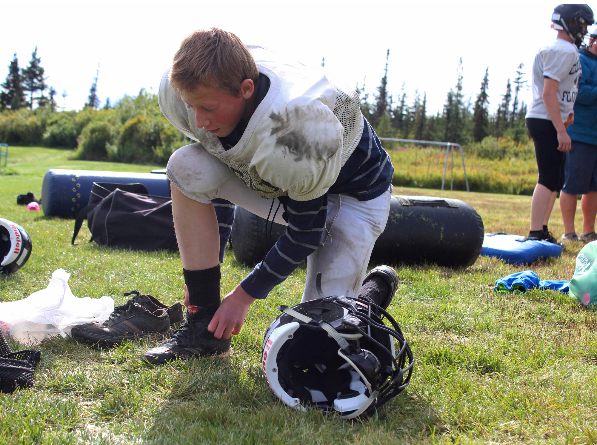 Foma Reutov, a freshman, ties up his shoes before a Cougars football practice Friday, Sept. 1, 2017 at McNeil Canyon Elementary in Fritz Creek, Alaska. The team, usually made up of a mix of students from the Russian Old Believer Villages Voznesenka, Razdolna and Kachemak-Selo, is in its fifth year as a varsity, 11-man program. (Photo by Megan Pacer/Homer News)