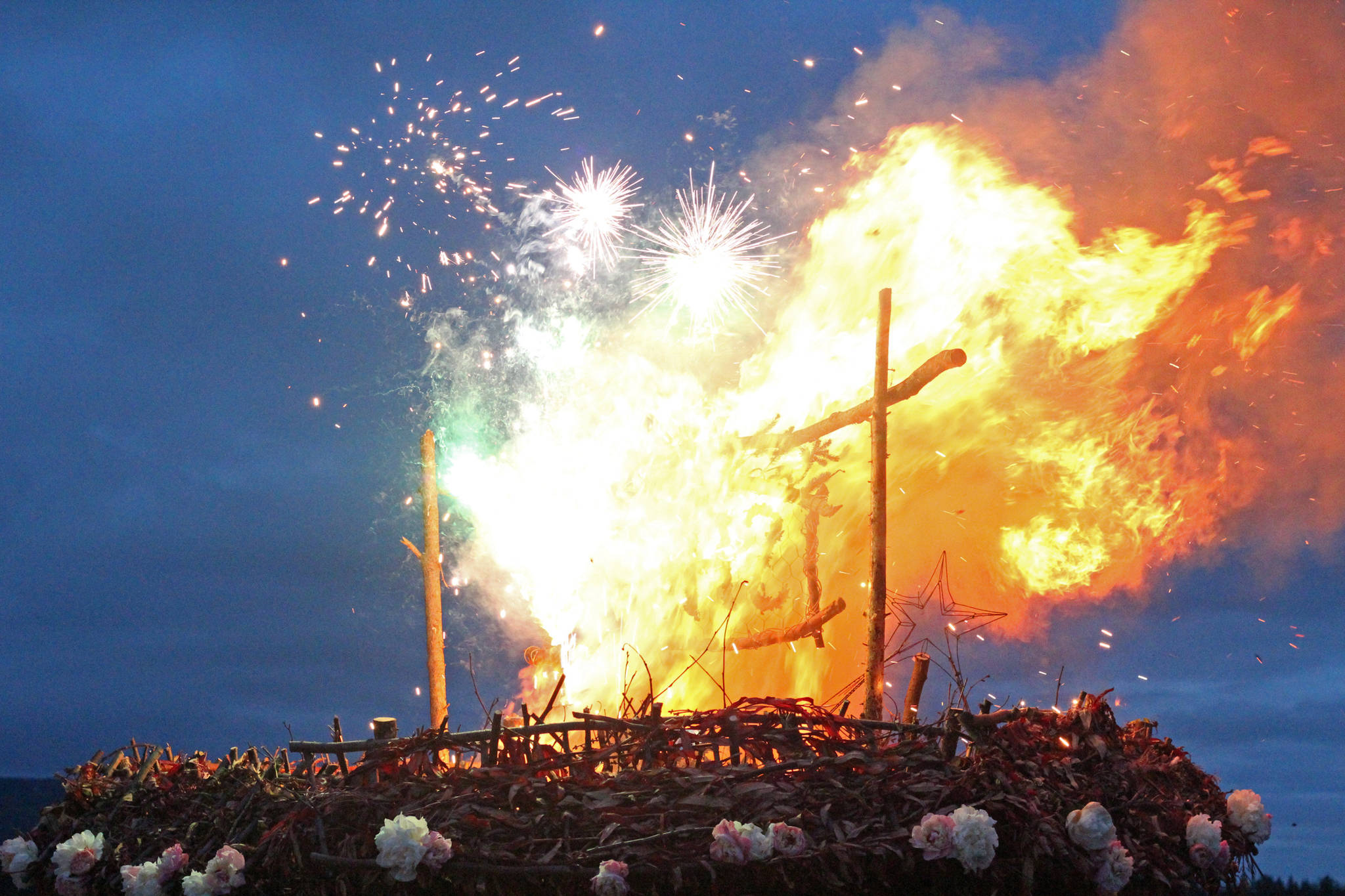 """Fireworks explode on top of this year's Burning Basket Project while it burns in a celebratory ceremony Sunday, Sept. 10, 2017 at Mariner Park in Homer, Alaska. This year's theme for the basket was """"Shine."""" (Photo by Megan Pacer/Homer News)"""
