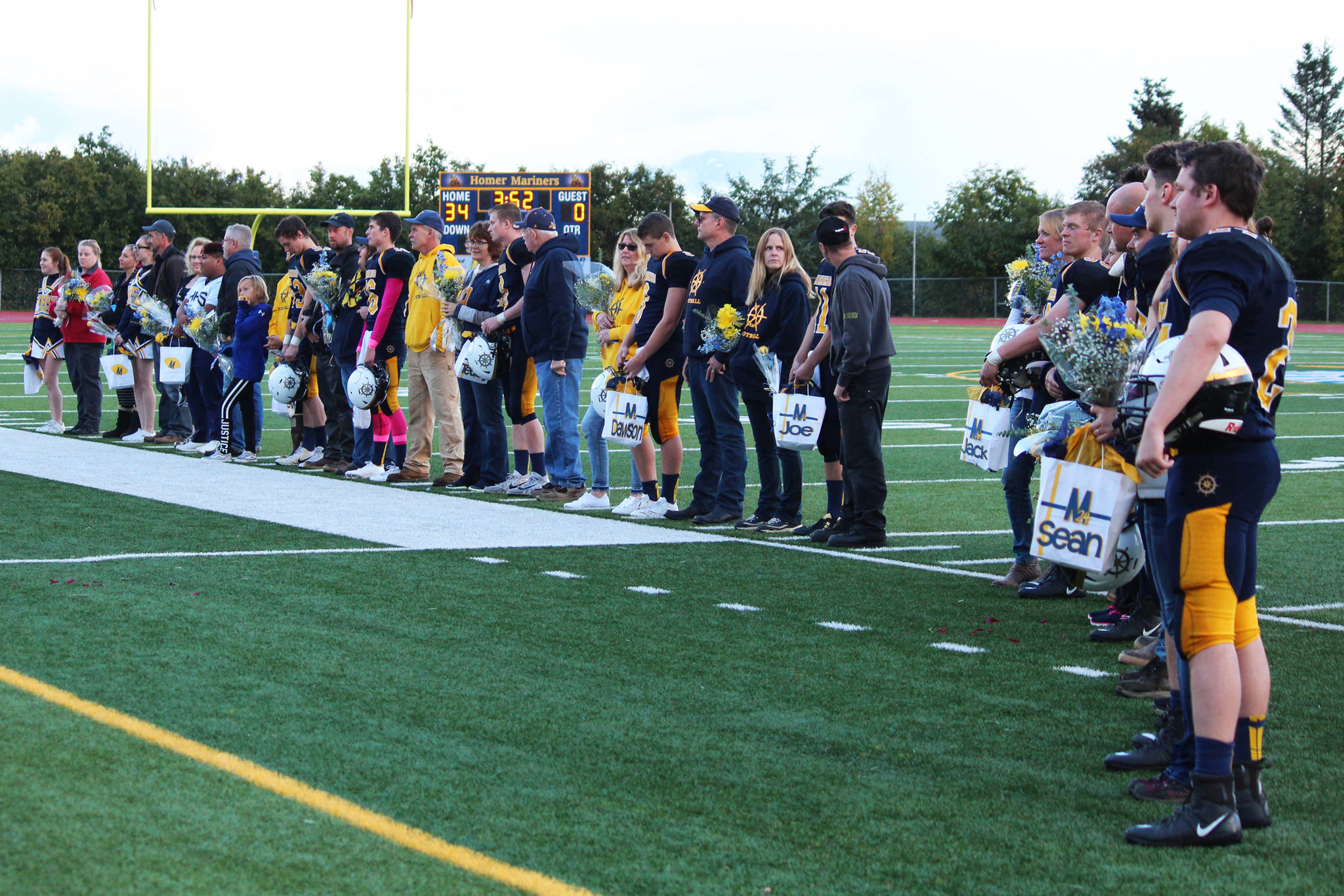 Seniors football players and cheerleaders from Homer High School stand on the field with their family members to be recognized during a senior night presentation during halftime of the game between the Mariners and the Head of the Bay Cougars on Friday, Sept. 29, 2017 at the Mariner field in Homer, Alaska. (Photo by Megan Pacer/Homer News)