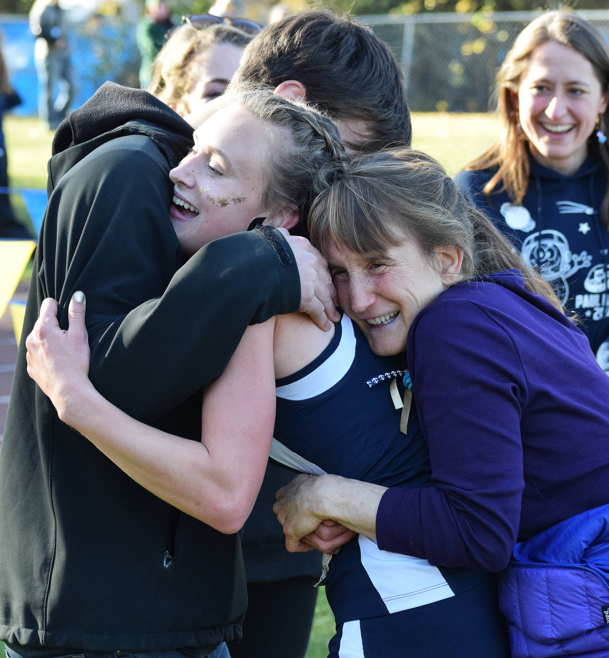Division II girls winner Autumn Daigle (center) receives hugs from her brother and mother Ann (right) Saturday, Sept. 30, 2017 at the ASAA First National Bank Alaska Cross-country State Championships at Bartlett High School in Anchorage, Alaska. (Photo by Joey Klecka/Peninsula Clarion)