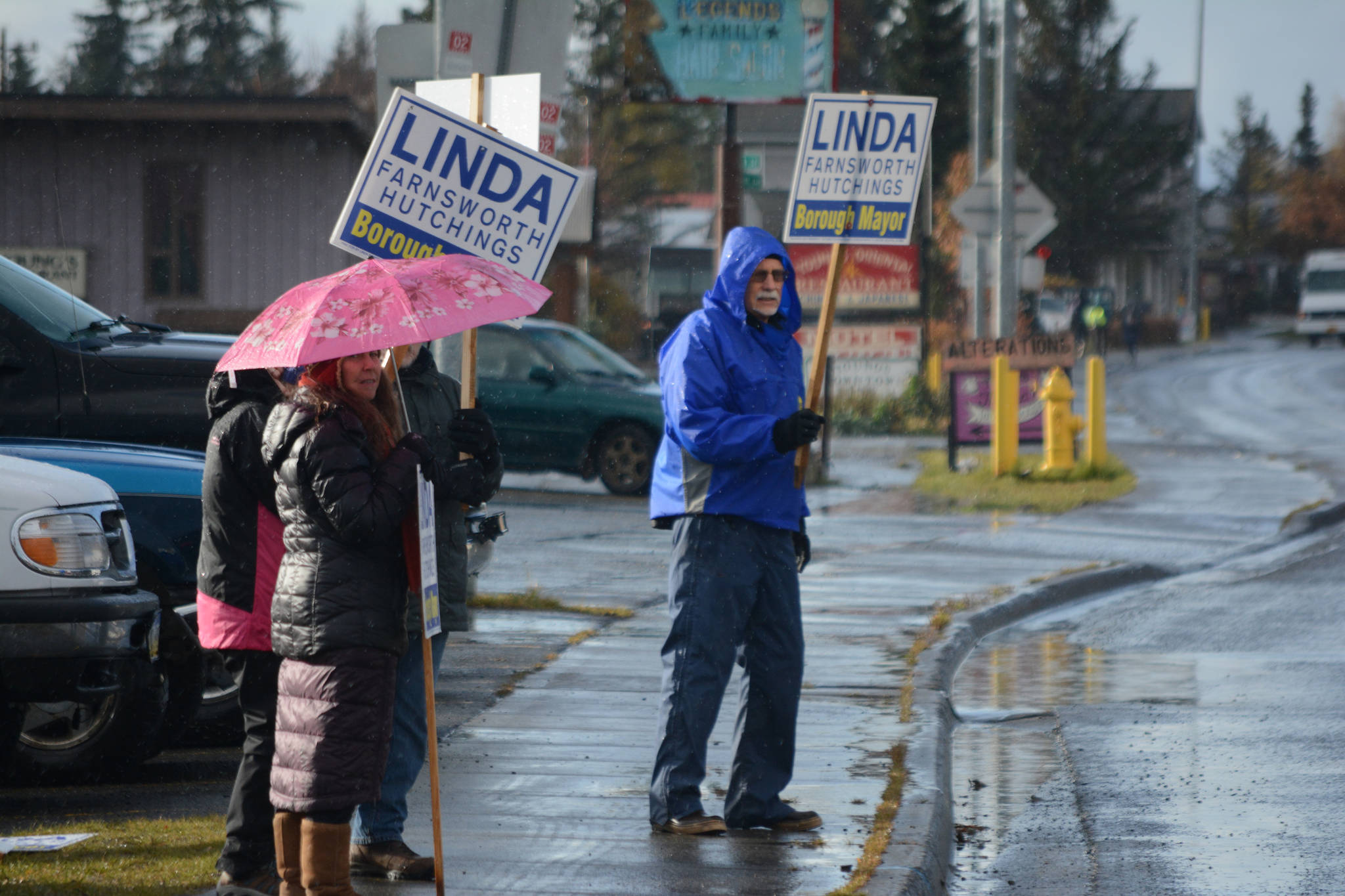 Wayne Aderhold, right, waves signs for Linda Hutchings on Tuesday afternoon, Oct. 24, 2017, in Homer, Alaska, on Pioneer Avenue. To his left are Marjorie Ringer, with umbrella, Lani Raymond and Ron Keffer. (Photo by Michael Armstrong, Homer News)