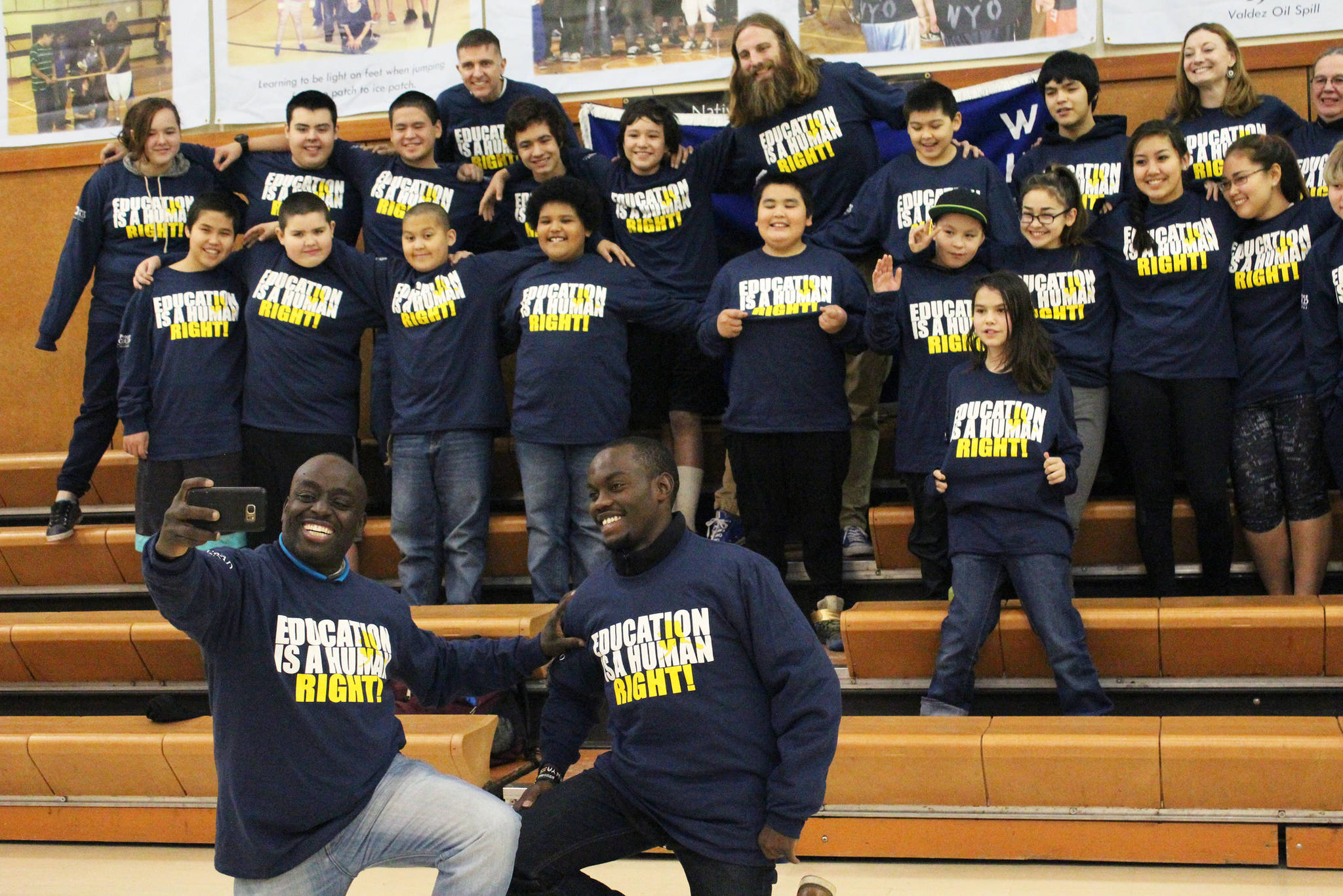 Chris Mburu, left, takes a selfie with Kimani Nyambura in front of several students from Port Graham School during a presentation there Thursday, Nov. 16, 2017 in Port Graham, Alaska. The pair spoke to students from four peninsula schools about the importance of education. Mburu and Nyambura are both from the same small village in Kenya, and were able to attend school through sponsorship. Mburu is not a human rights lawyer working for the United Nations. (Photo by Megan Pacer/Homer News)