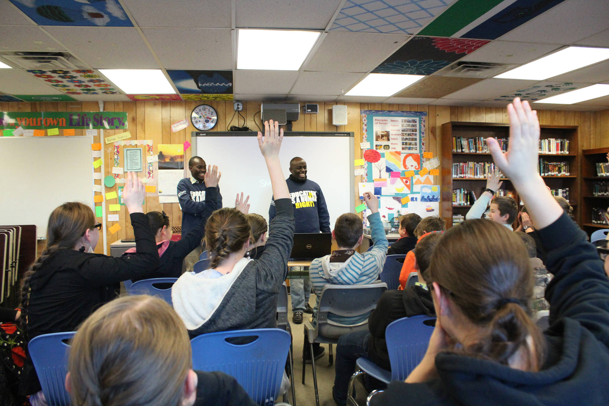 Human rights lawyer and Kenya native Chris Mburu, right, and Kimani Nyambura, left, laugh as the majority of a room full of Razdolna students raise their hand to respond to the question of how many of them have the last name Basargin, during a presentation Friday, Nov. 17, 2017 at the school in Razdolna, Alaska. Mburu, who started a foundation to put Kenyan children through school after being sponsored himself, gave presentations to several Kenai Peninsula schools this week along with Nyambura, one of the students who has been able to go to school thanks to the foundation. (Photo by Megan Pacer/Homer News)
