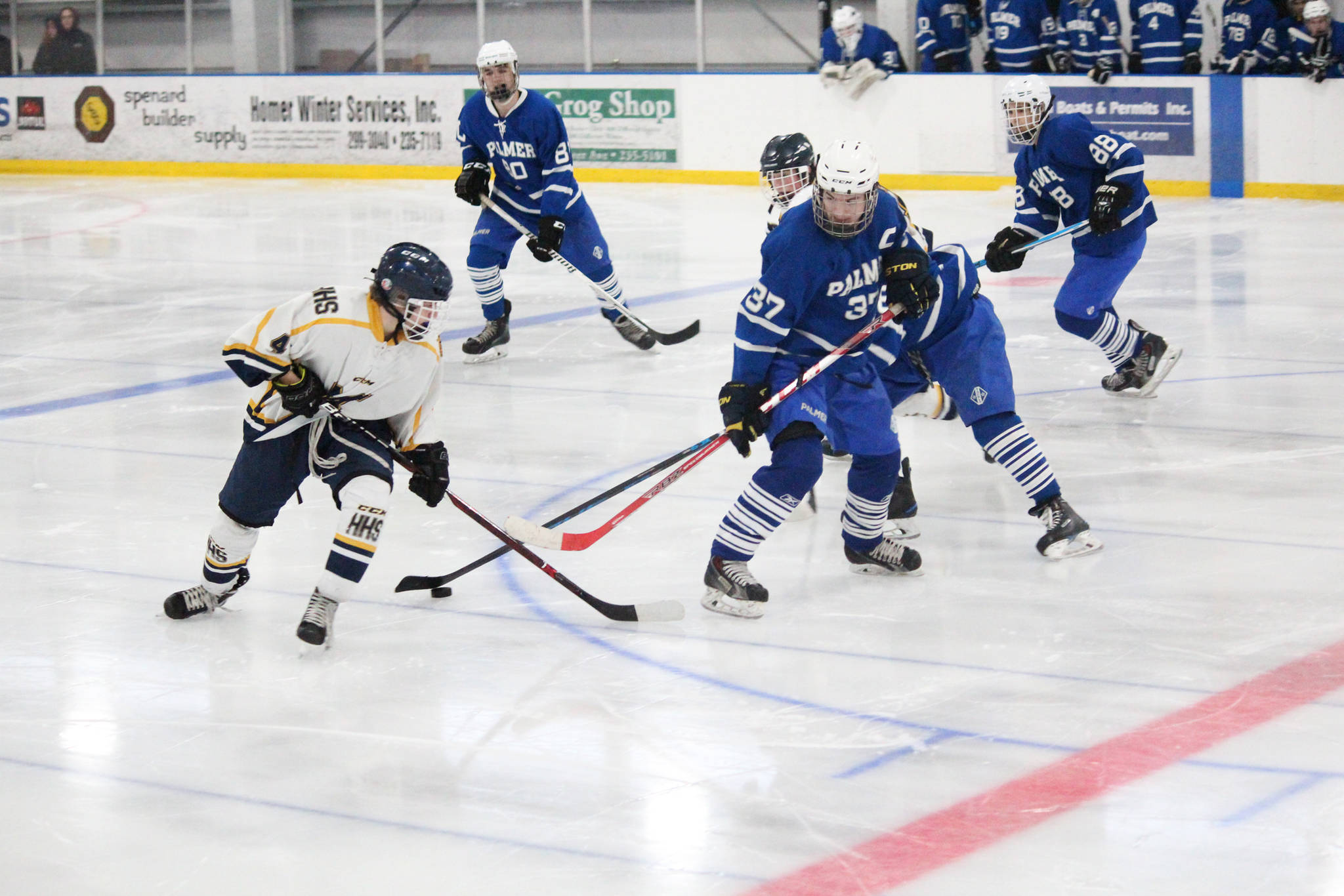 Homer's Lee Lowe tries to get the puck away from several Palmer High School skaters during their game Saturday, Dec. 2, 2017 at Kevin Bell Ice Arena in Homer, Alaska. The Mariners swept all three Mat-Su Valley teams they played over the weekend, moving to 3-0 in conference play. (Photo by Megan Pacer/Homer News)
