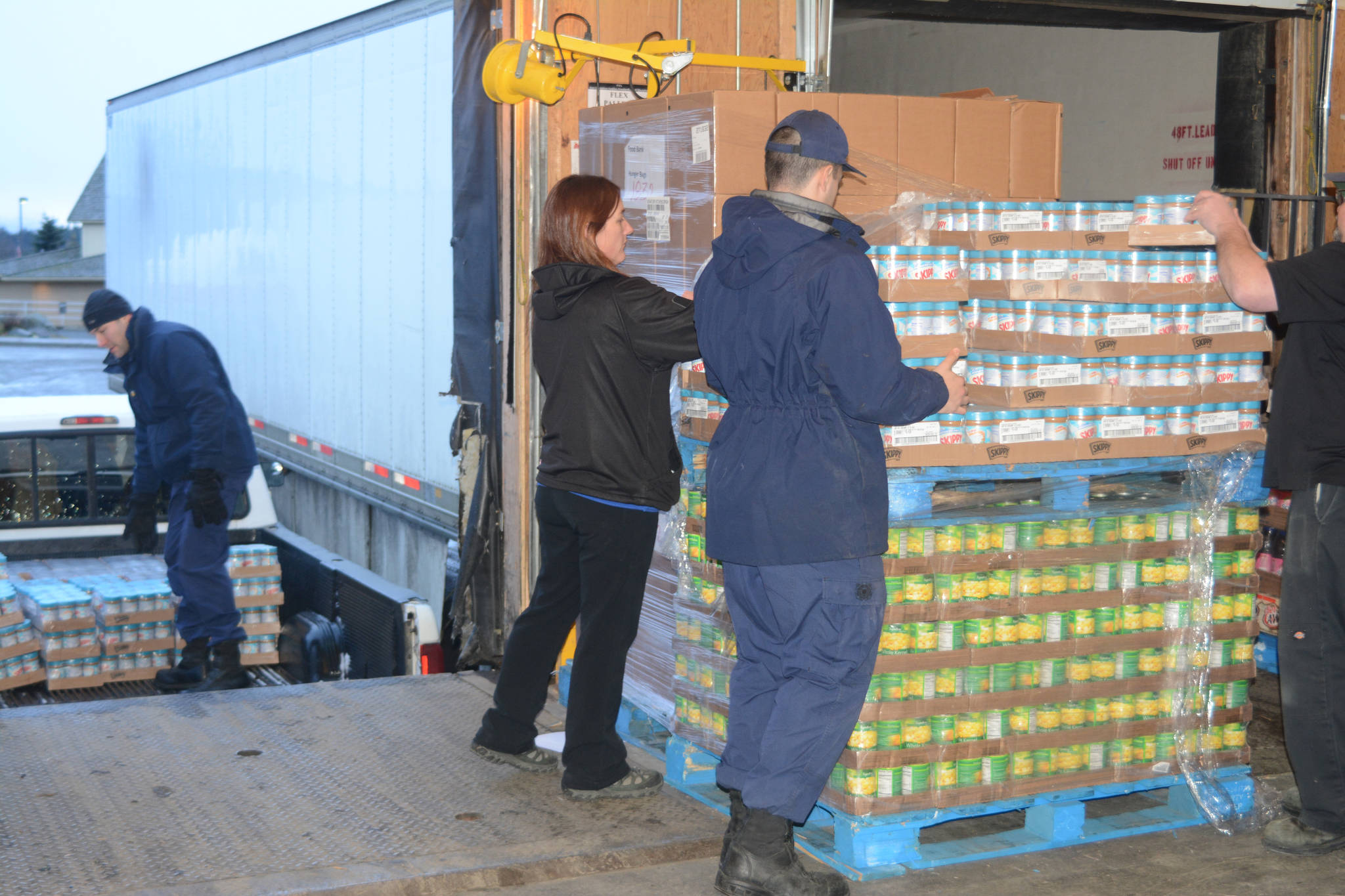 """U.S. Coast Guard Cutter Naushon crew member Jordan Dorchin, right, helps Homer Safeway assistant store manager Tiffany Biggs, center, load Hunger Bag food onto a truck as his fellow crew member James Bannon, left, packs the truck Tuesday, Dec. 5, 2017. The Coast Guard members delivered food to the Homer Community Food Pantry Tuesday morning that had been purchased by Safeway customers as part of its Hunger Bag project. Store Manager Bob Malone said about 1,300 bags at $10 each had been sold at the Homer store since Nov. 1. Through a national program, Safeway sells the bags and donates food to charities chosen by local stores. Pallets of food are organized at the Anchorage warehouse and sent to Homer. """"This year, from what I understand, the need is more than normal,"""" Malone said."""