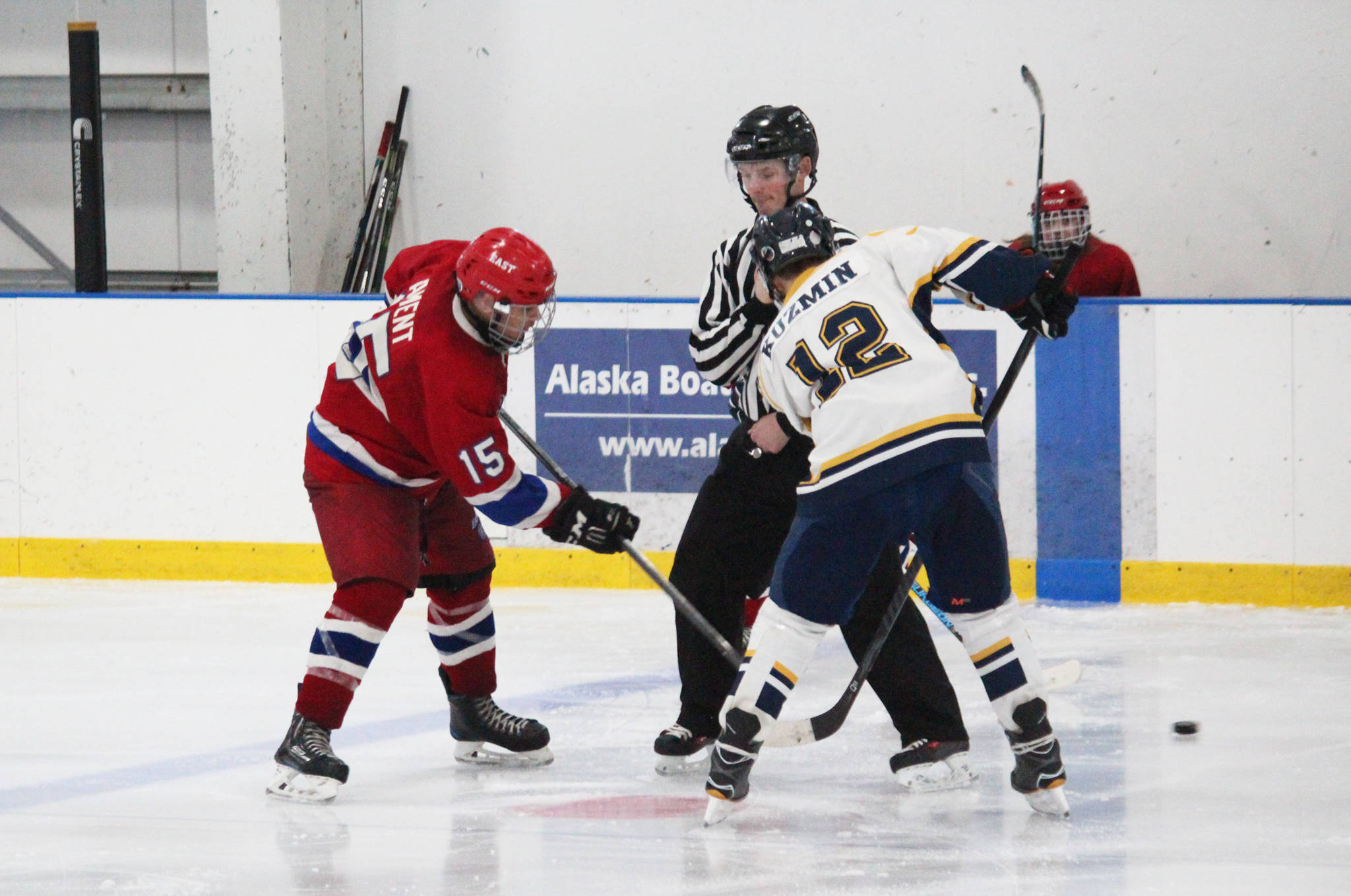 Homer senior Dimitry Kuzmin faces off against East Anchorage High School's Devon Ament during their game Saturday, Jan. 20, 2018 at the Kevin Bell Arena in Homer, Alaska. The Mariners beat East, whose team was missing four players, 10-1. (Photo by Megan Pacer/Homer News)