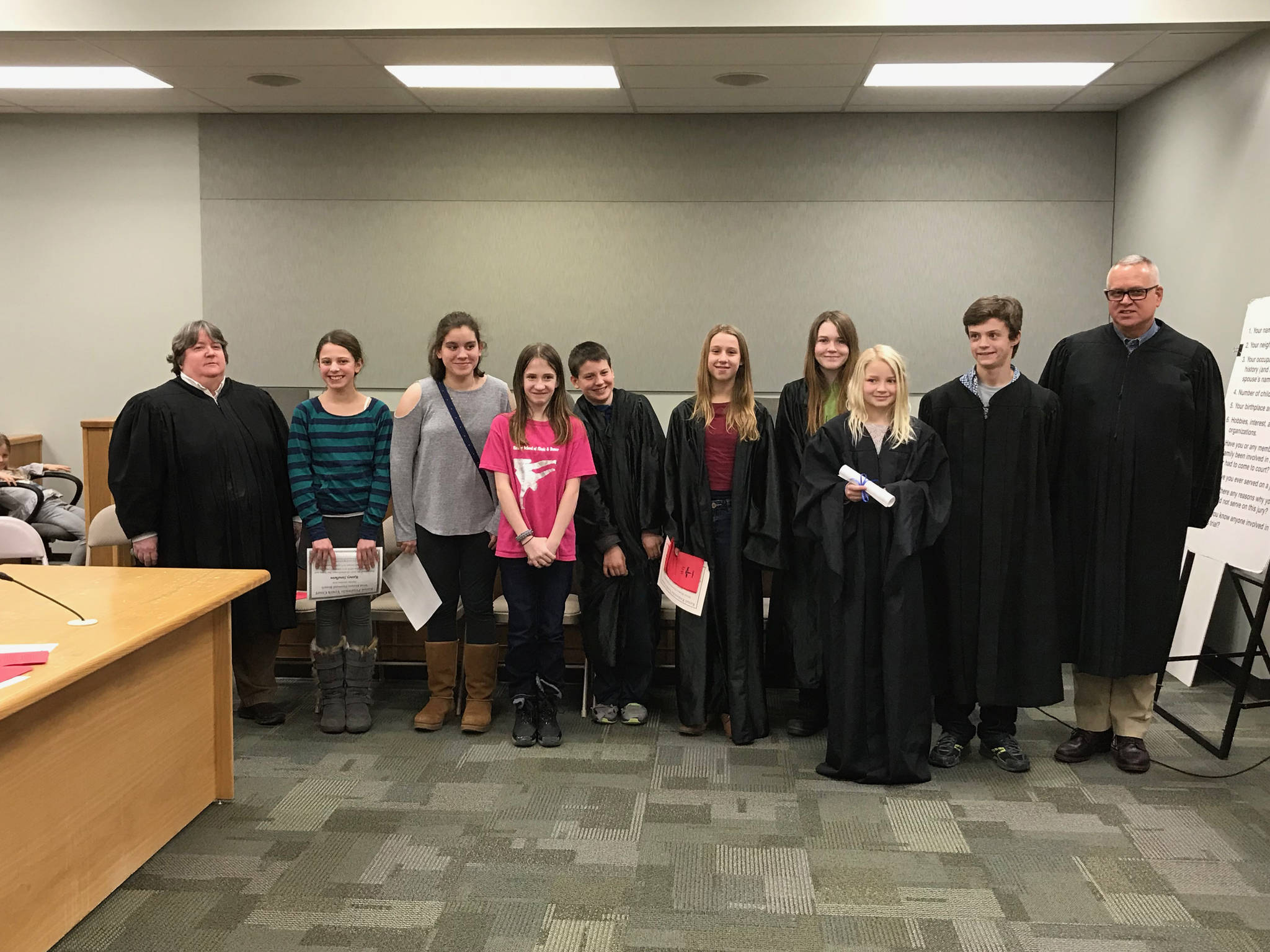 New judges and attorneys for the West Homer Elementary School / Fireweed Academy Youth Court pose after induction ceremonies at the Homer Courthouse on Monday, Jan. 22, 2018. Homer Disctrict Court Judge Margaret Murphy, far left, and Kenai Superior Court Judge Charles Huguelet, far right, administered the oaths of office. (Photo provided)