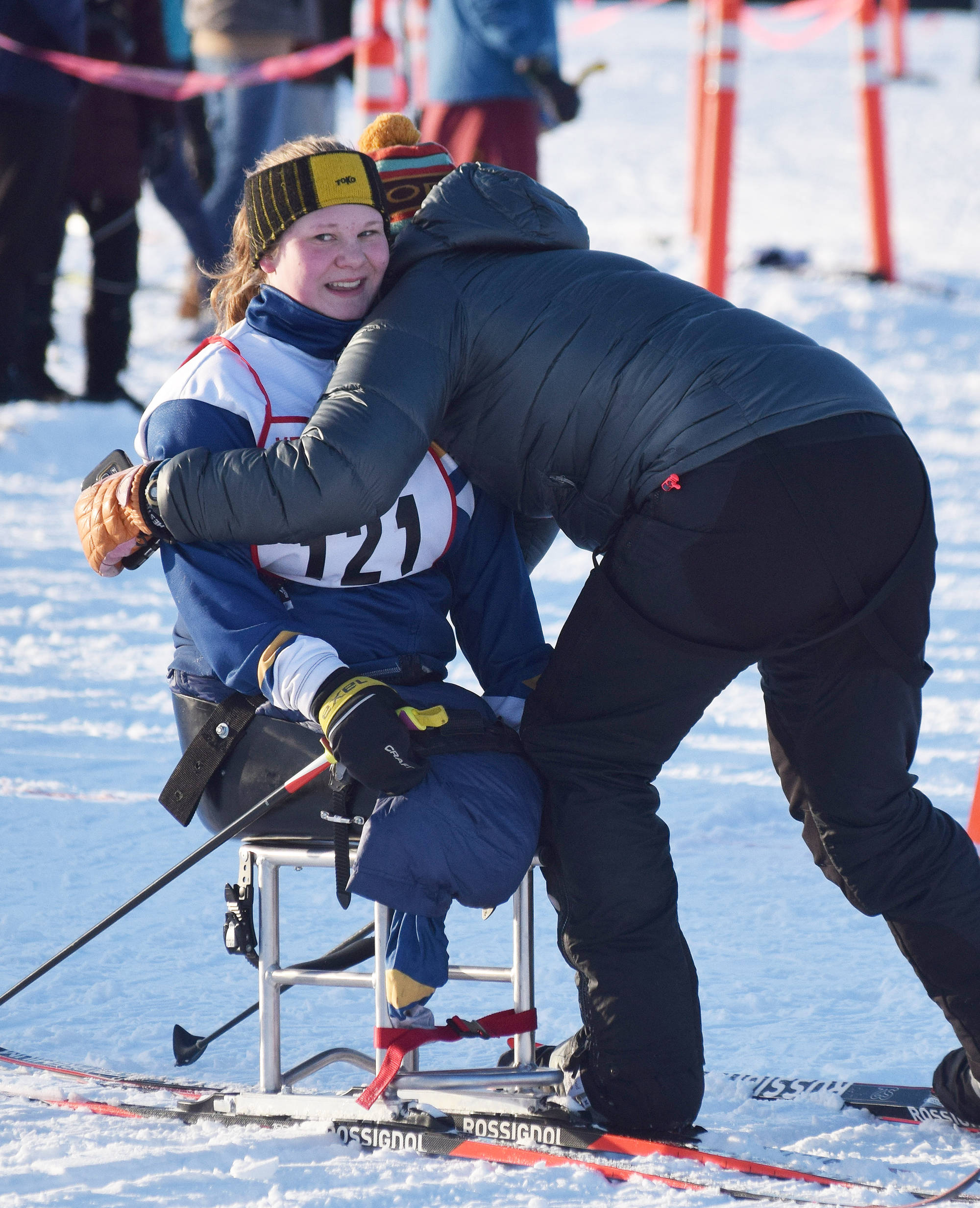 Angelica Haakenson receives a hug from Homer assistant coach Megan Corazza Friday afternoon in the Kenai Klassic races at the Tsalteshi Trails in Soldotna. (Photo by Joey Klecka/Peninsula Clarion)