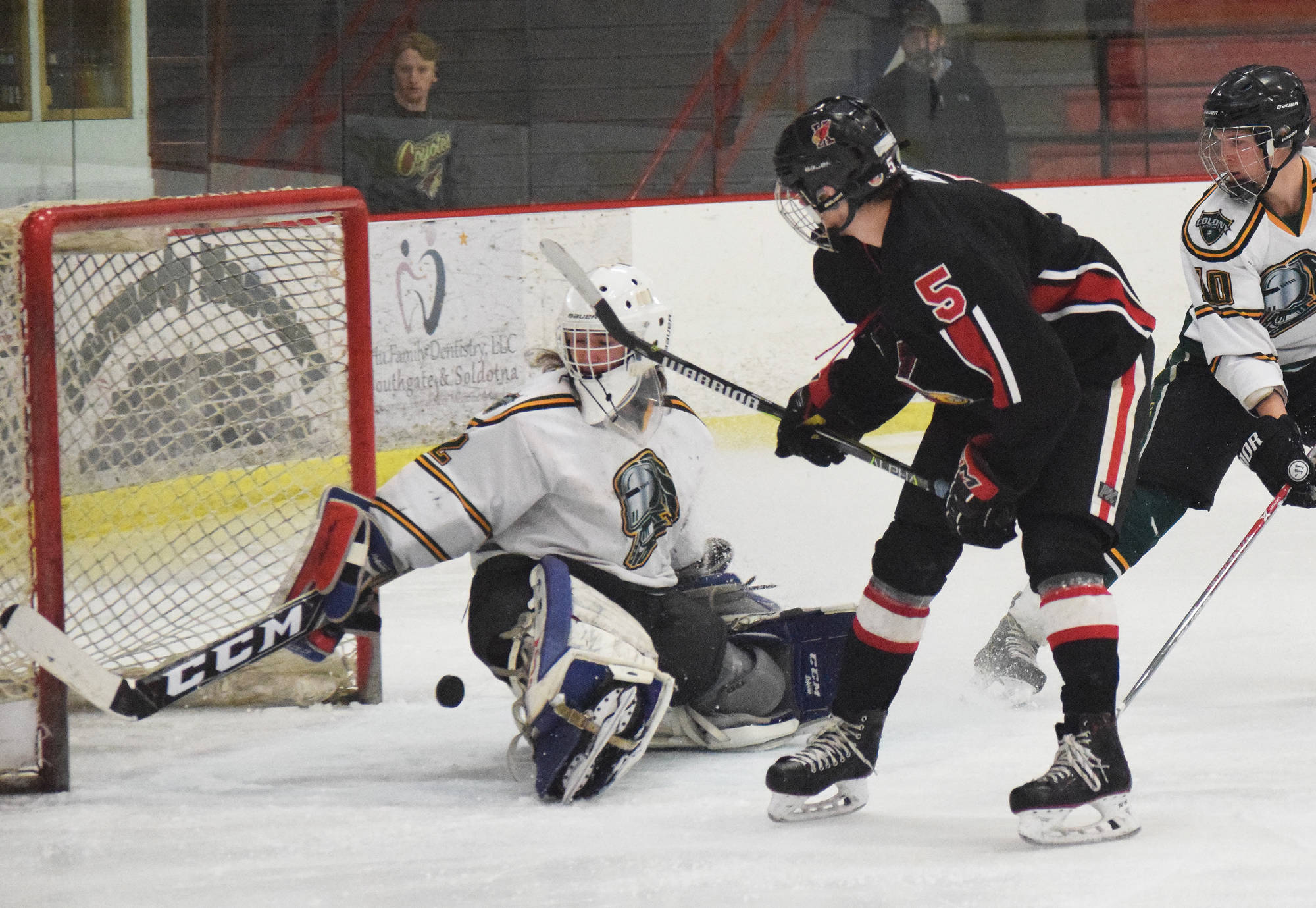 Kenai Central skater Levi Mese (5) watches as the puck nearly slips by Colony goalie Cole Doss, Friday in a North Star Conference tournament semifinal at the Soldotna Regional Sports Complex. (Photo by Joey Klecka/Peninsula Clarion)