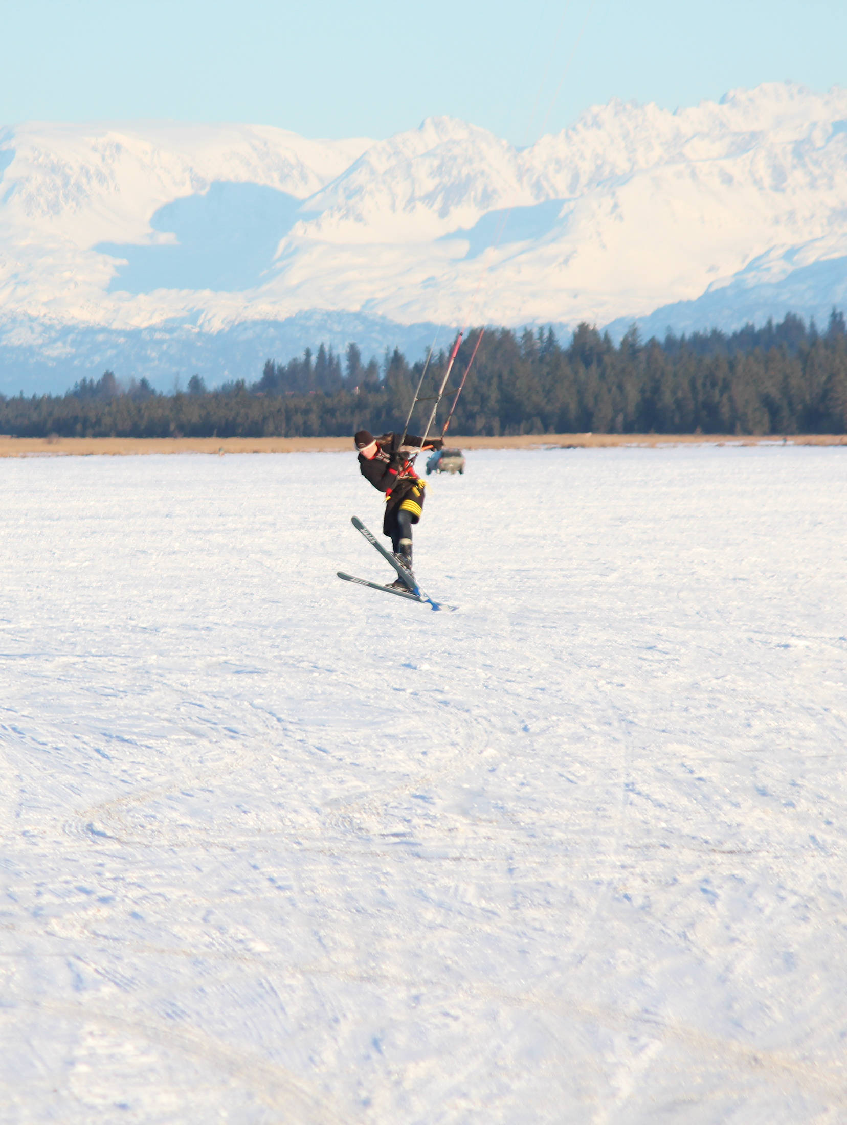 A man catches some air while snowkiting, or kite skiing, on Beluga Lake on Saturday, Feb. 3, 2018 in Homer, Alaska. Outdoor enthusiasts use the power provided by a large kite on a windy day to glide across snow or ice. (Photo by Megan Pacer/Homer News)