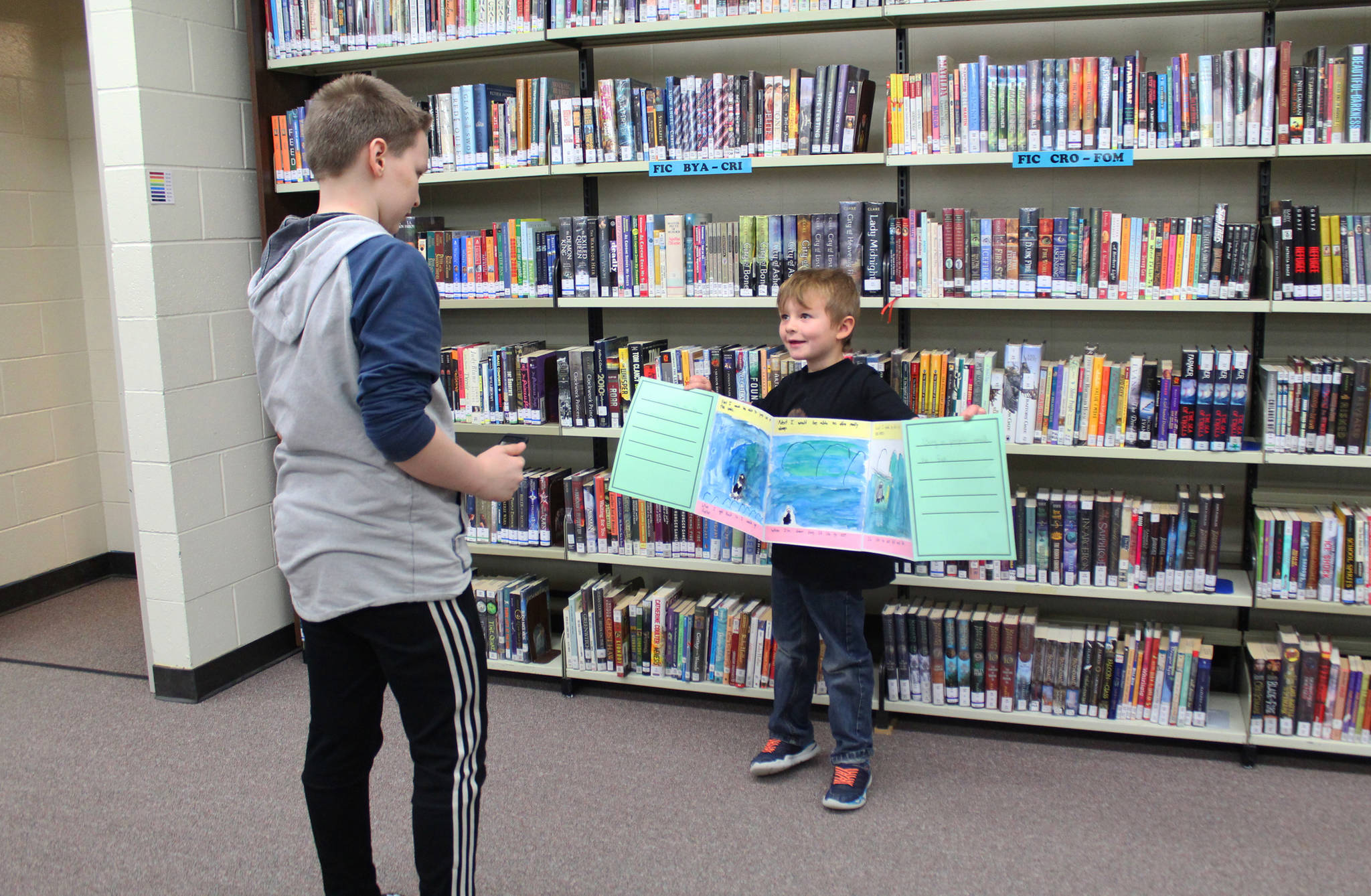 Seventh graders Payton Edens gives guidance to first grader Sawyer Johnson while they work on filming a reading of a book they worked on together during the second day of a mentor program Friday, Feb. 2, 2018 at Homer Middle School. (Photo by Megan Pacer/Homer News)