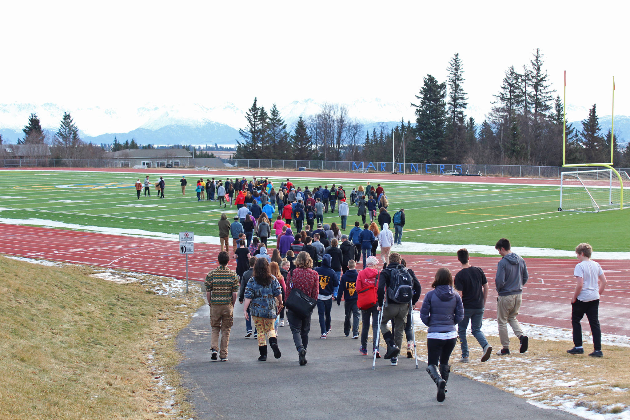 About 100 Homer High School students gather on the football field during a walkout staged Wednesday, Feb. 21, 2018 to protest for safer schools and honor the students killed in the Valentine's Day mass shooting in Parkland, Florida. The students formed the number 17 with their bodies on the field. (Photo by Megan Pacer/Homer News)