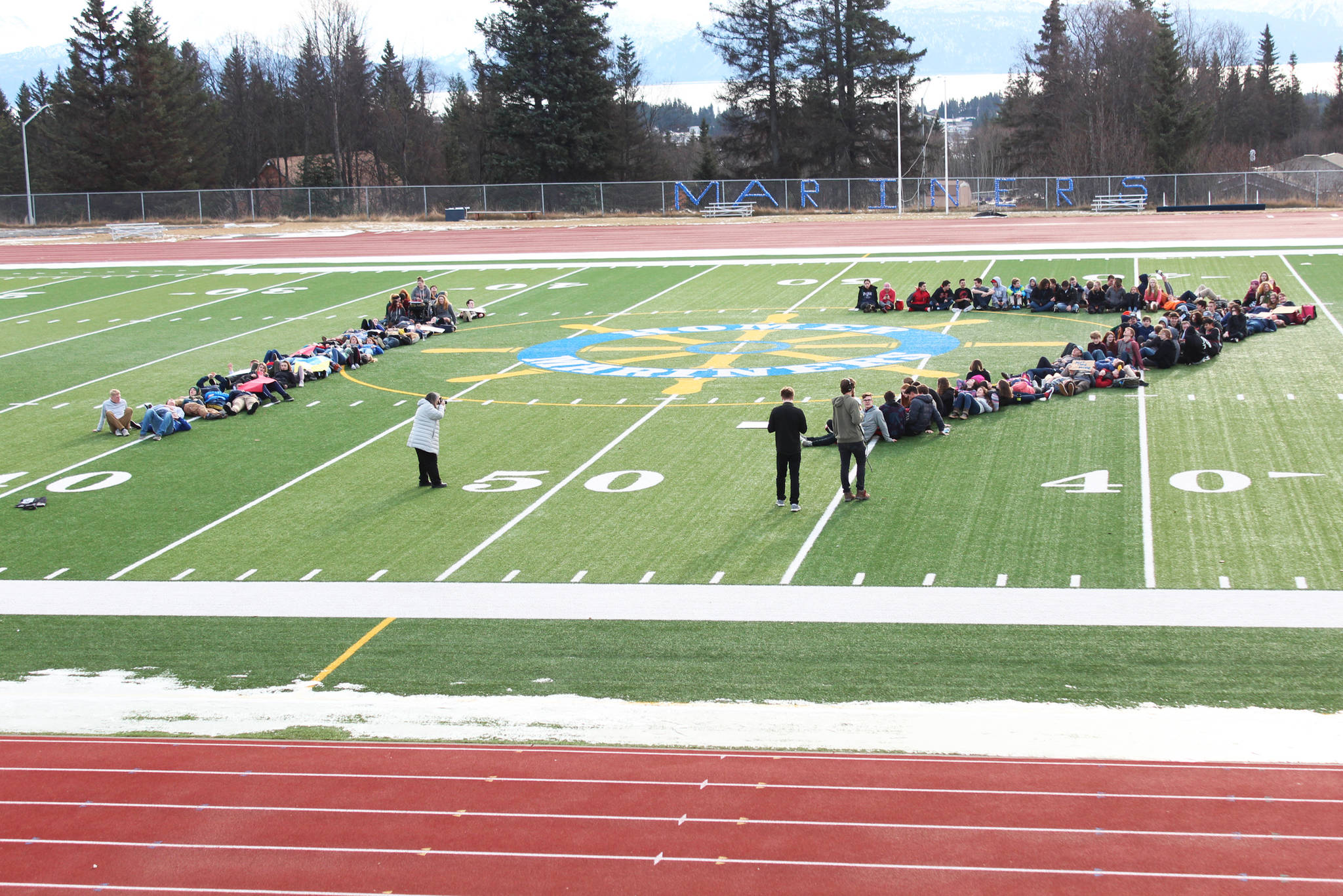 About 100 Homer High School students lie down on the school's football field to form the number 17 on Wednesday, Feb. 21, 2018, to honor the students who were killed in the Feb. 14 mass shooting in Parkland, Florida. The Homer students staged a walkout at noon to advocate for safer schools. (Photo by Megan Pacer/Homer News)
