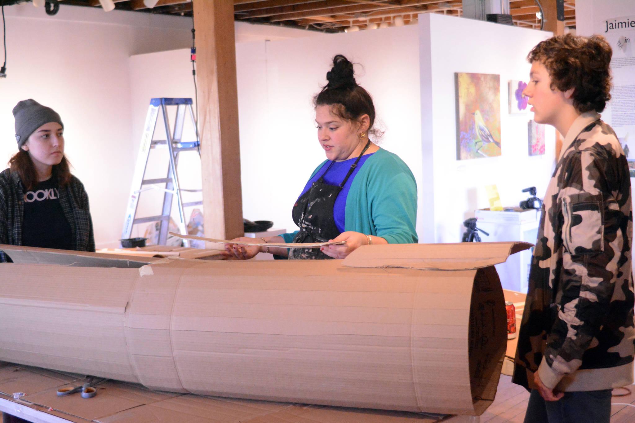 TOP: Artist in Residence Jaimie Warren, center, discusses how to make a log costume with Mila Stickrod, left, and Alex Franklin, right, at her temporary studio at Bunnell Street Arts Center. The Brooklyn, New York, artist visits Homer this month. (Photo by Michael Armstrong, Homer News)