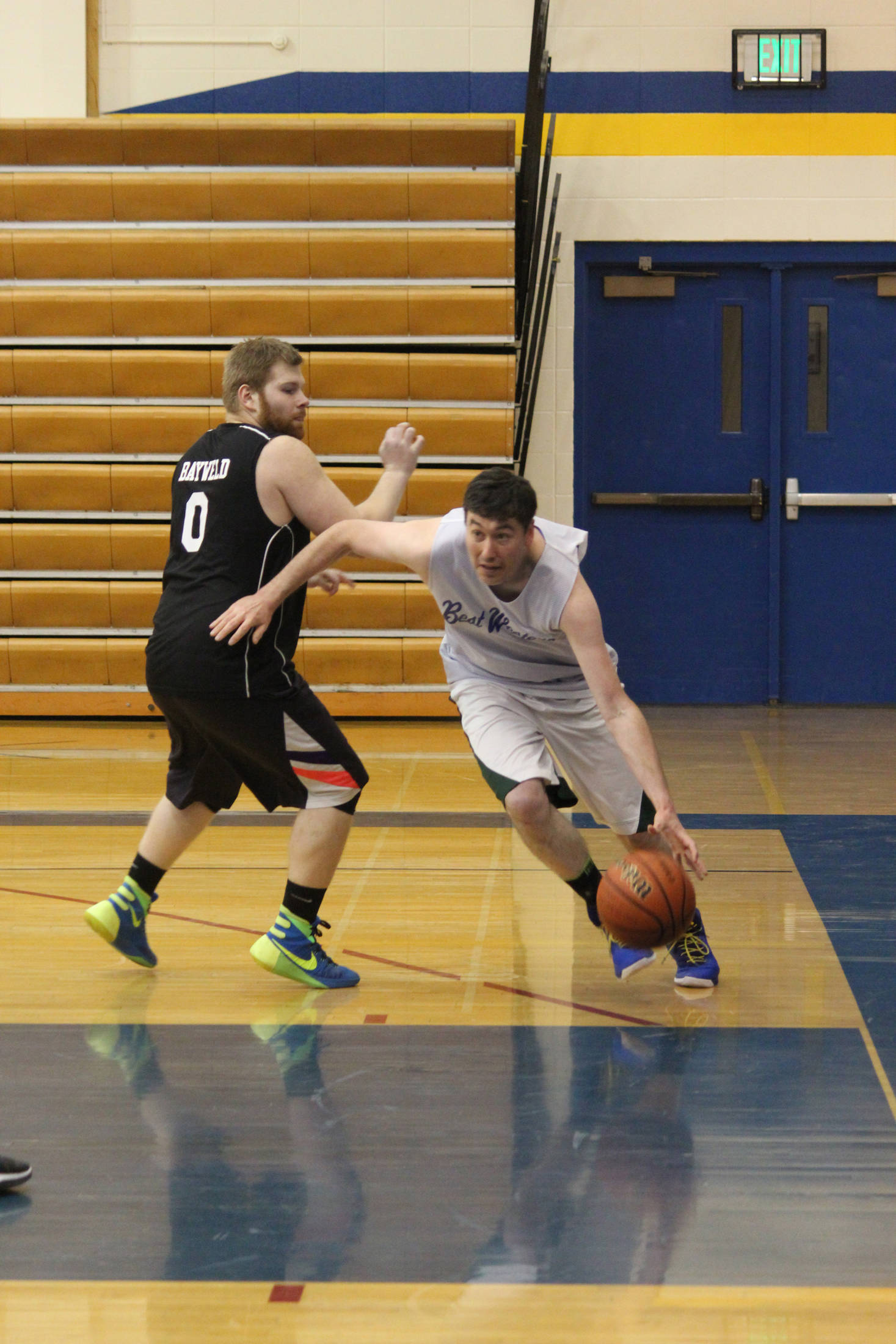 Josh Garvey (right) dribbles past Martin Molodih during the Homer city basketball league's championship game Monday, March 5, 2018 at Homer High School. (Photo by Megan Pacer/Homer News)