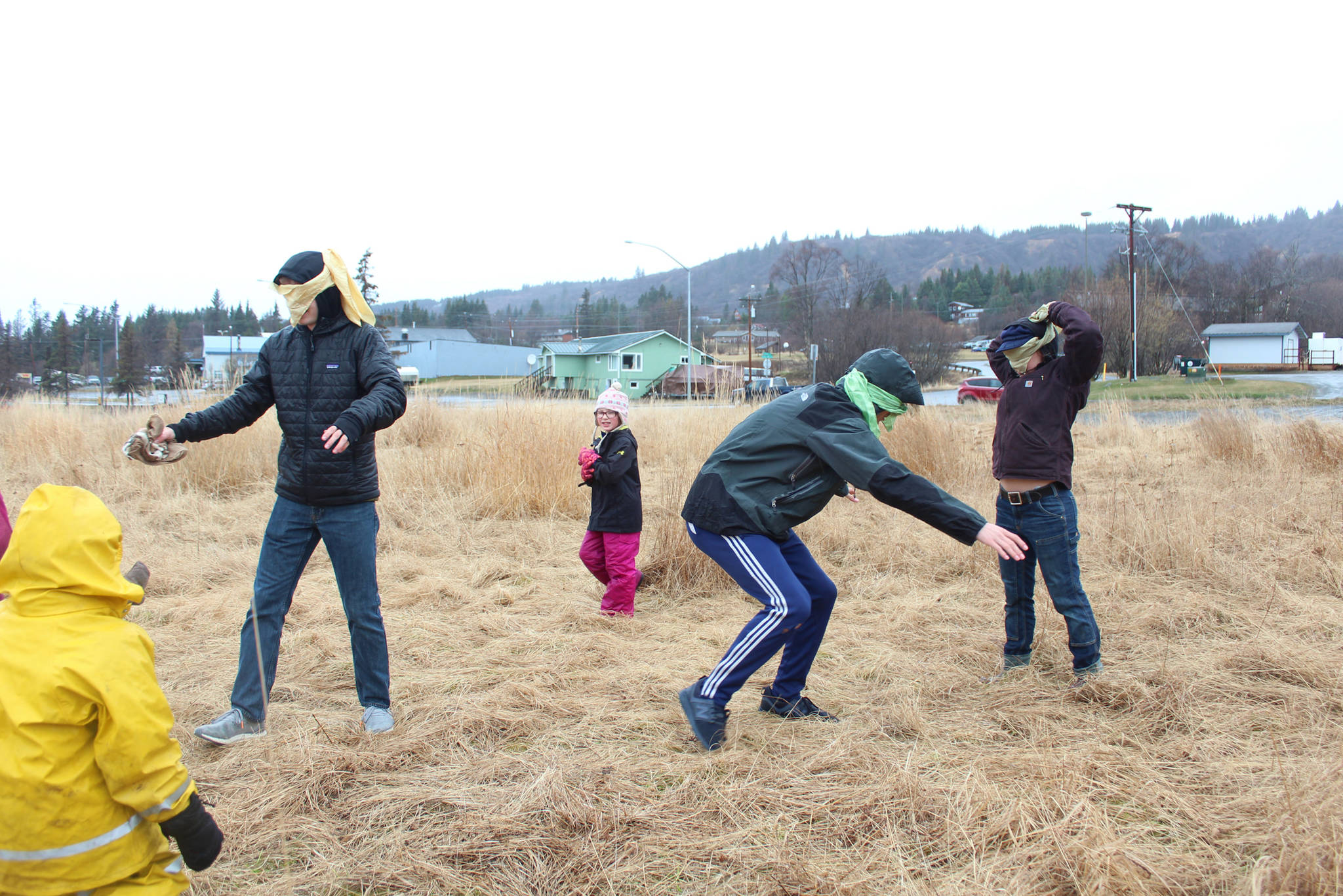 """Homer High School students Simon Dye (left) and Charlie Menke (center), along with Lindsay Seneff play a game with Little Fireweed Students in which they pretend to be foxes that can only find """"mice"""" in a field by following their squeaks on Tuesday, April 24, 2018 in Homer, Alaska. (Photo by Megan Pacer/Homer News)"""