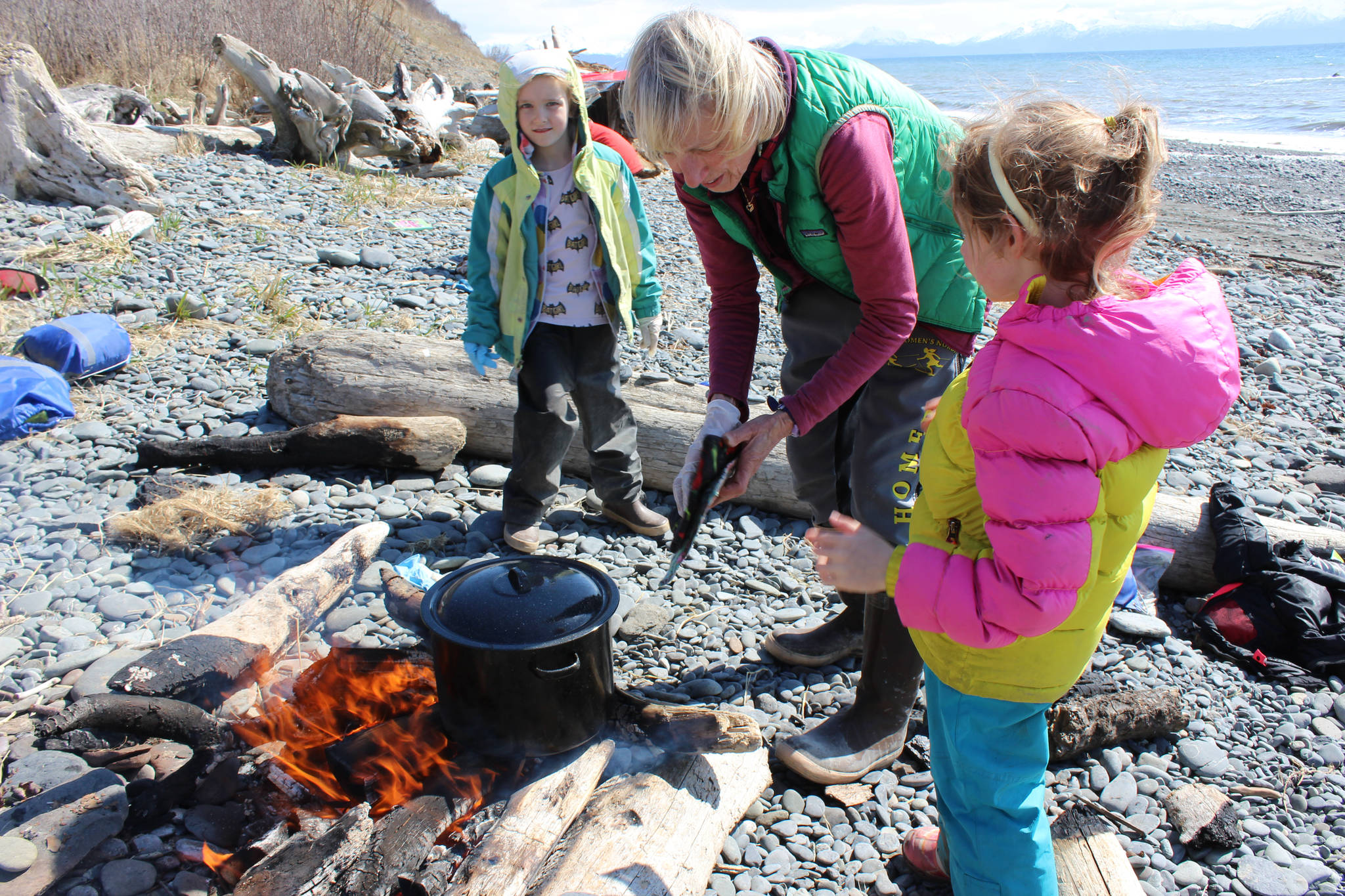 A May 2 outing for students in the Kenai Peninsula School District's Wilderness Explorers program in Homer is an opportunity for volunteer Tania Spurkland (center) to teach Estelle Velsko (left) and Allie Barker (right) how to prepare stinging nettles over a campfire. (Photo by McKibben Jackinsky)
