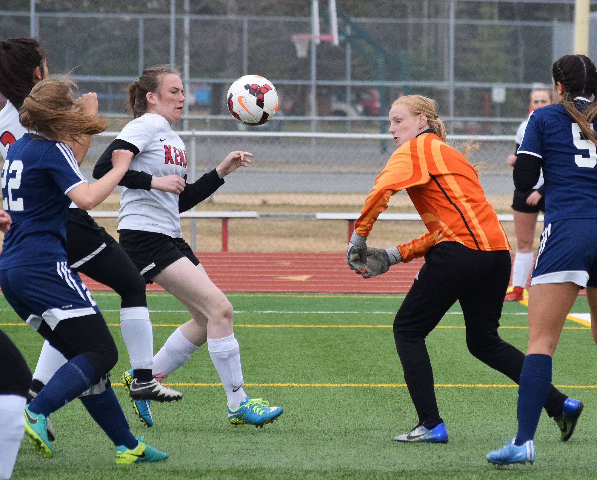 Homer goalkeeper Kelli Bishop (in orange) knocks the ball away on a Kenai Central rush Tuesday evening at Ed Hollier Field in Kenai. (Photo by Joey Klecka/Peninsula Clarion)