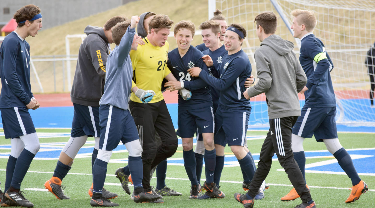 Photo by Jeff Helminiak/Peninsula Clarion Homer goalie Tucker Weston (in yellow) celebrates with teammates after defeating Soldotna in the Peninsula Conference semifinals Friday, May 18 at Soldotna High School.