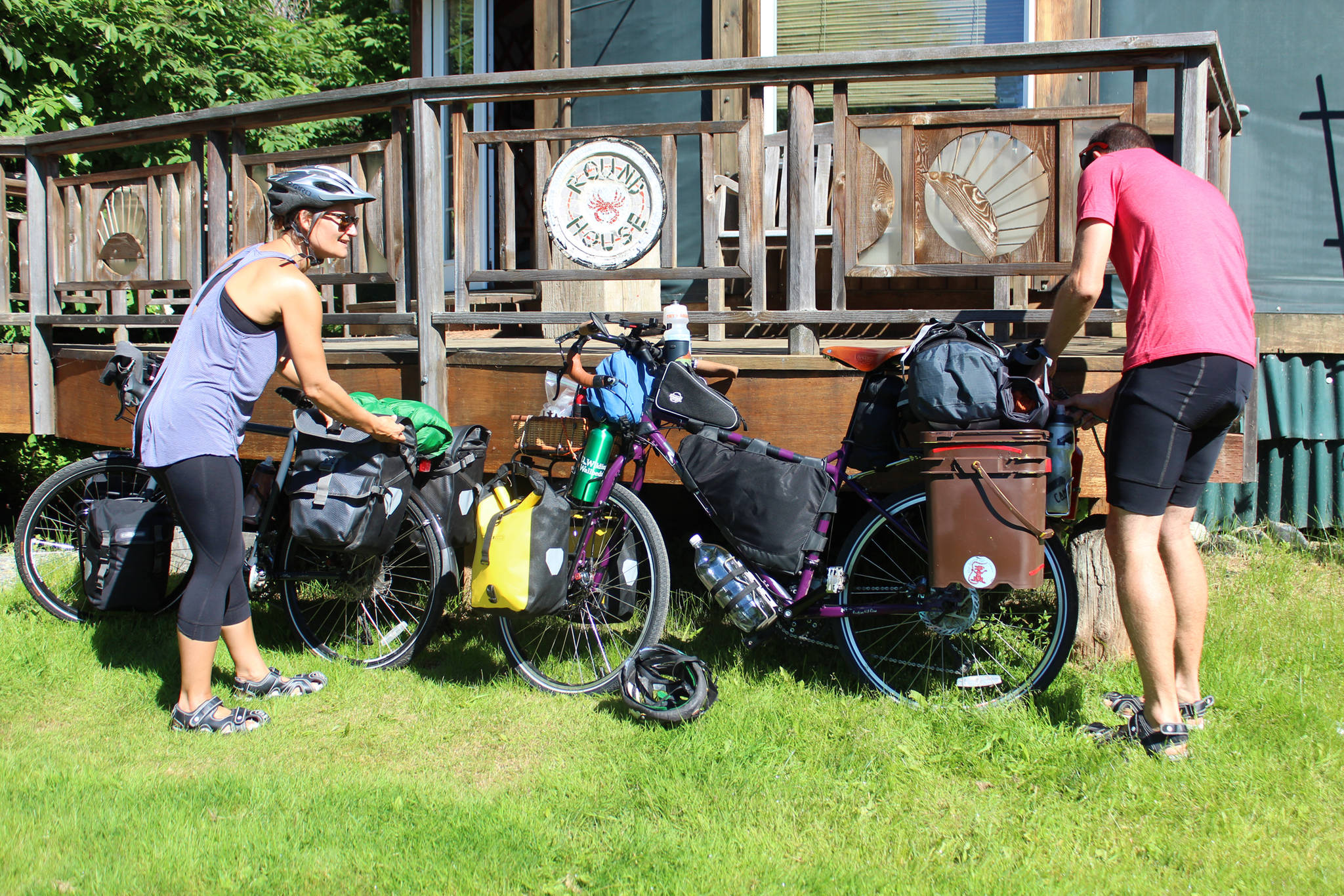 Sophie George and Chris Haag put the finishing touches on their bikes before setting off on a two-year trek from Alaska to Argentina on Monday, July 2, 2018 on Hidden Way in Homer, Alaska. The husband and wife packed up their life in Utah prior to the adventure. (Photo by Megan Pacer/Homer News)