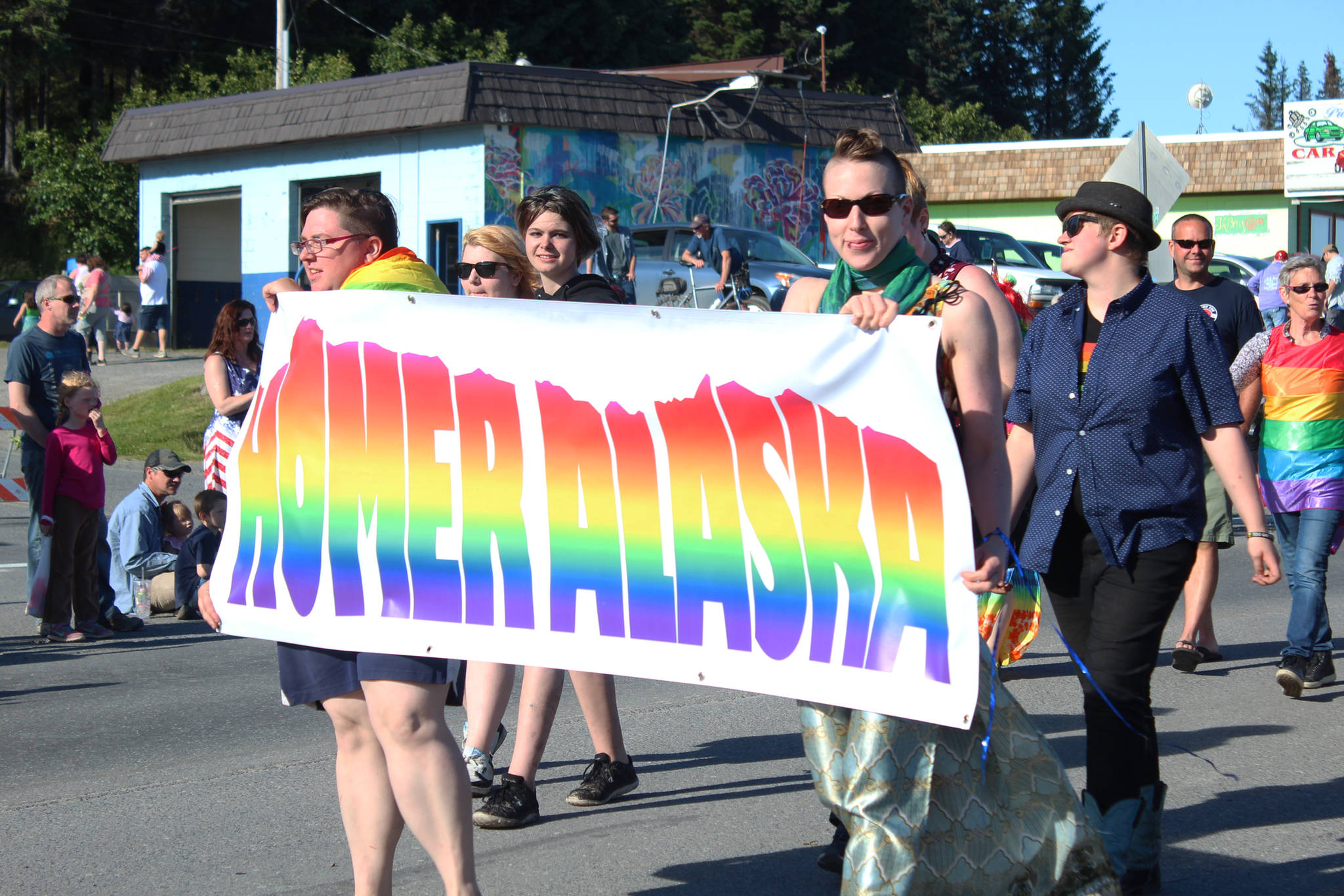 A small crowd of people march in the LGBTQ Pride section of the annual Independence Day parade Wednesday, July 4, 2018 along Pioneer Avenue in Homer, Alaska. (Photo by Megan Pacer/Homer News)