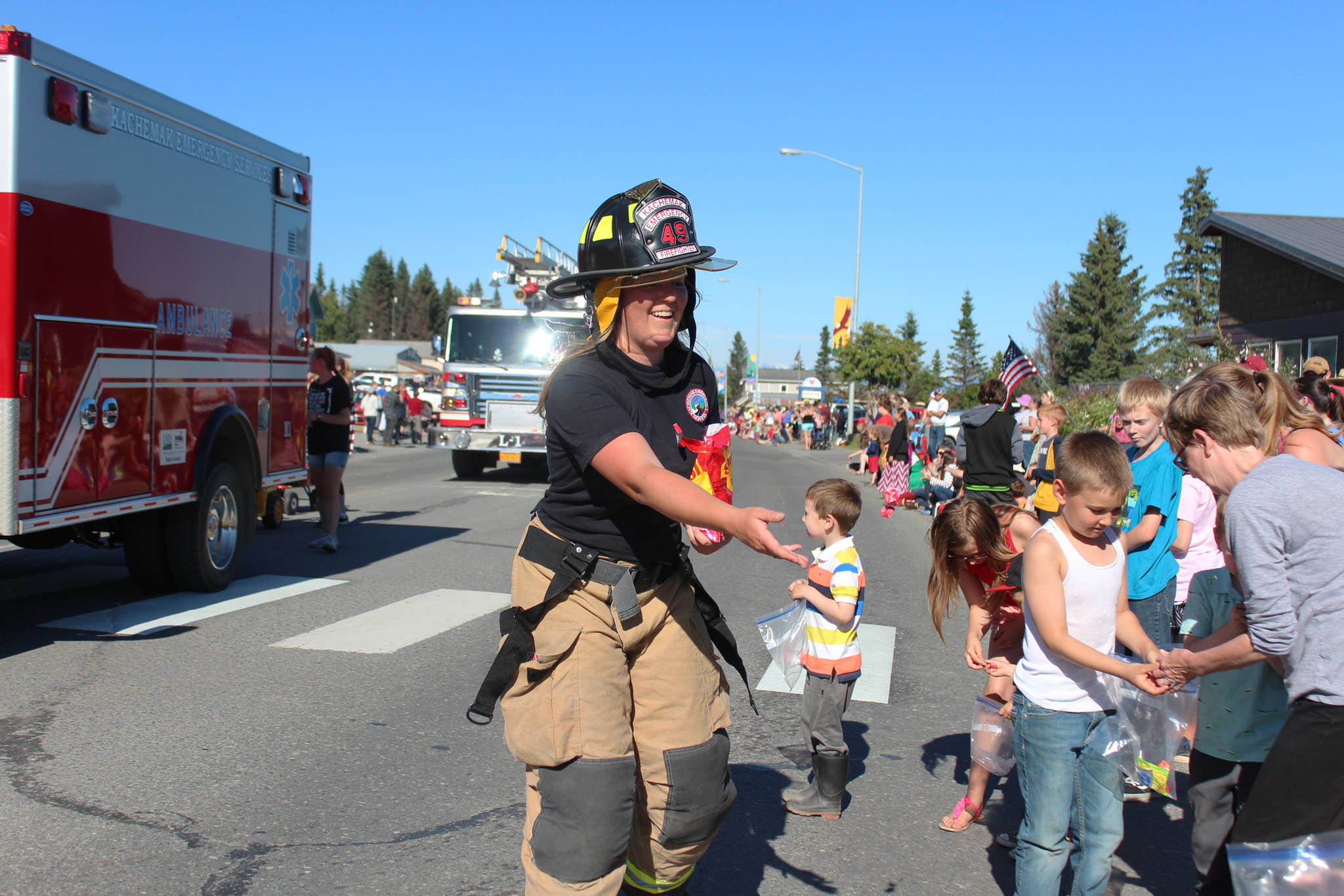 A member of Kachemak Emergency Services tosses candy to eager children along Pioneer Avenue during this year's Independence Day parade Wednesday, July 4, 2018 in Homer, Alaska. (Photo by Megan Pacer/Homer News)
