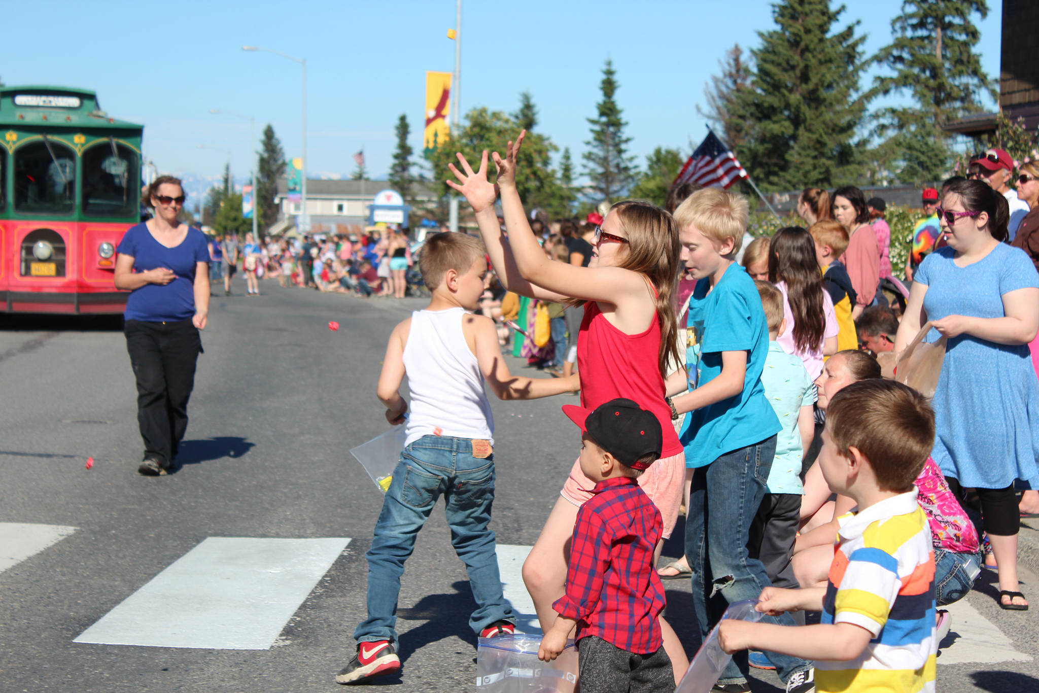 Children scramble for candy tossed from passing floats and parade walkers during this year's Independence Day parade Wednesday, July 4, 2018 on Pioneer Avenue in Homer, Alaska. (Photo by Megan Pacer/Homer News)