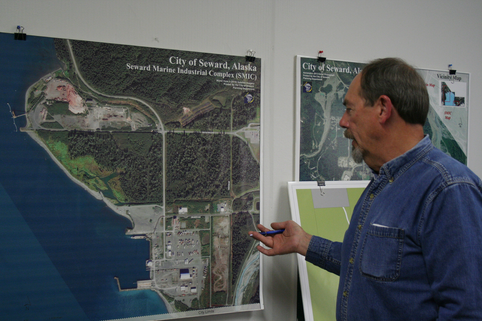 Seward Community Development Director Ron Long discusses the city's plans for the Seward Marine Industrial Center across Resurrection Bay from its population center in front of a photo of the shipyard and surrounding area.