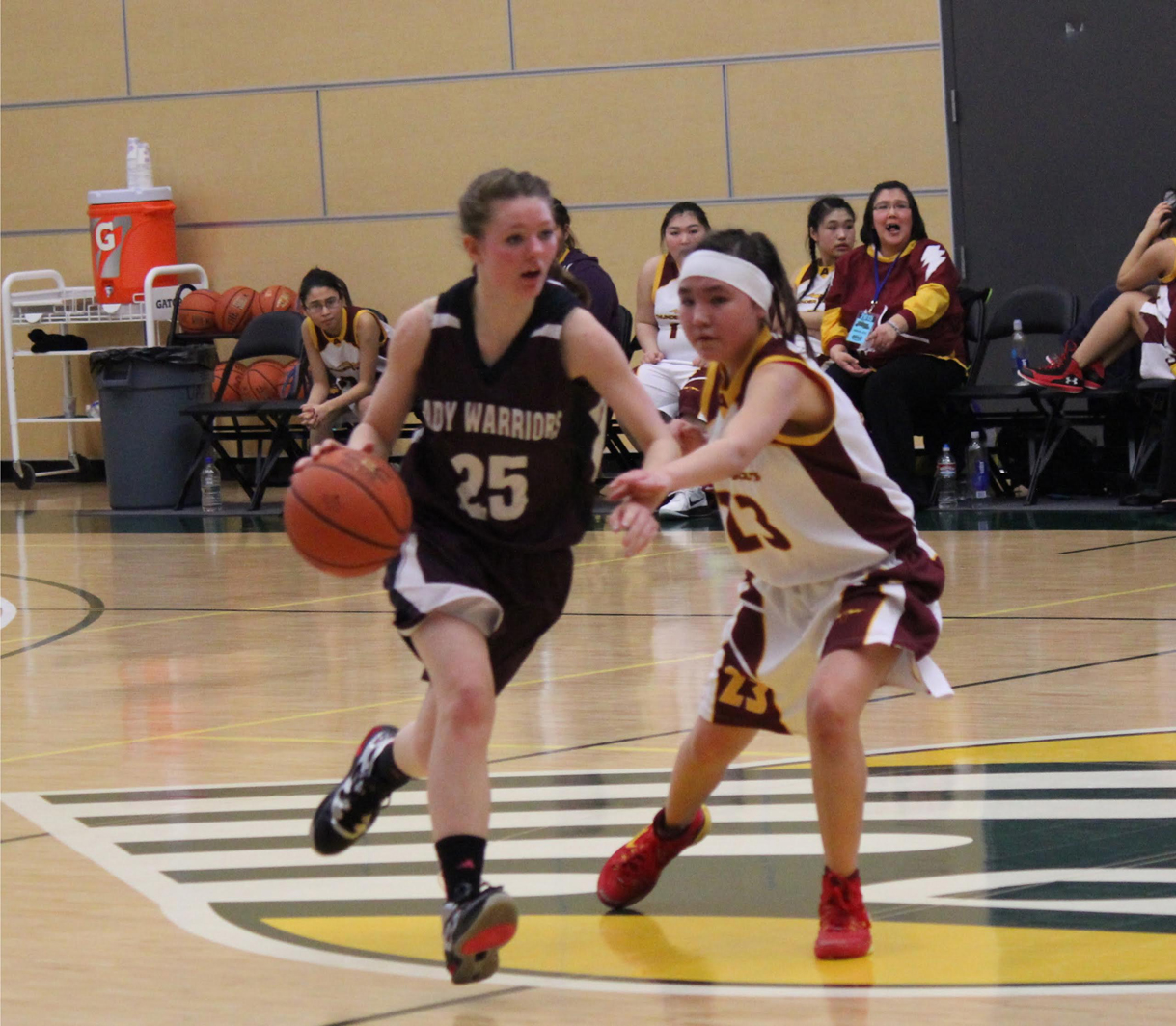 Nikolaevsk Warrior Megan Hickman, 25, maneuvers the ball down the court beyond the reach of Akiak Thunderbolt's Miranda Demientieff during team competition at the State 1A tournament in Anchorage on Saturday.-Photo by McKibben Jackinsky