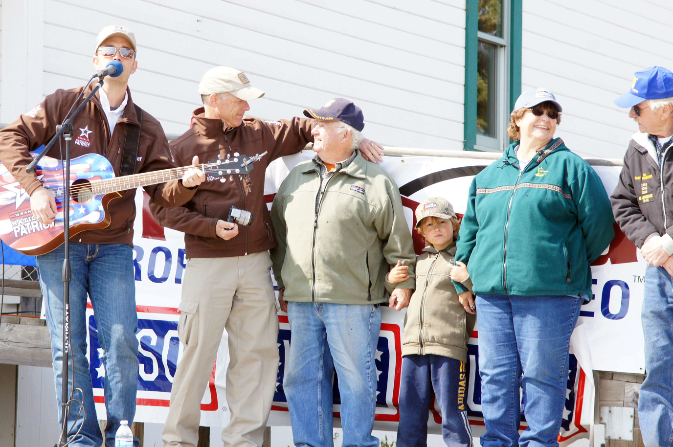 Nashville singer Lucas Hoge, left, performs during the American 300's presentation of the Wrangler National Patriot Memorial Day Tour in the NOMAR parking lot on Sunday. Rob Powers, second from left, of American 300 honors Ben Mitchell, standing with his grandson Willem, wife Kate and Bill Sheldon of American Legion Post 16.  -Photo provided