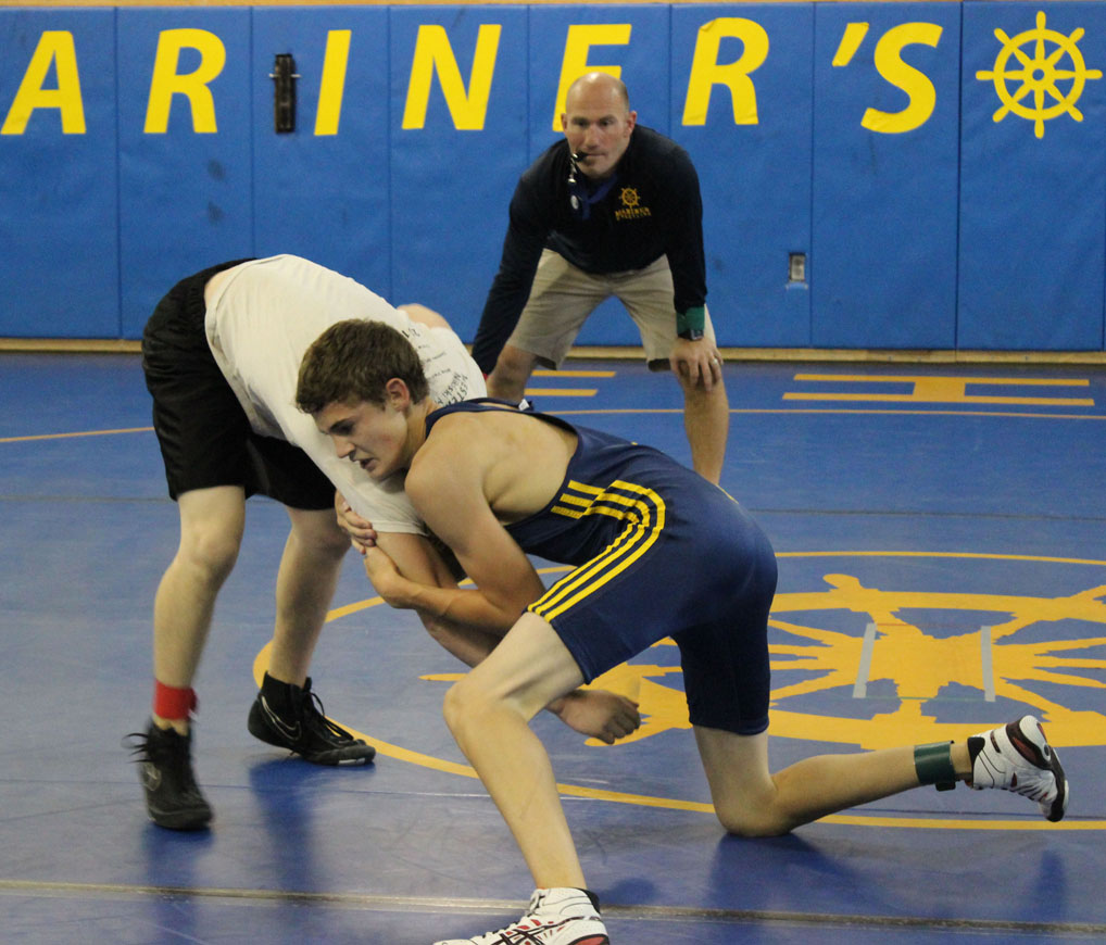 Mariner Jared Brant, who placed fifth at state last year, wrestles his Nikiski opponent during scrimmages in the Mariner mat room on Saturday. Mariner Coach Chris Perk referees.-Photo by McKibben Jackinsky, Homer News