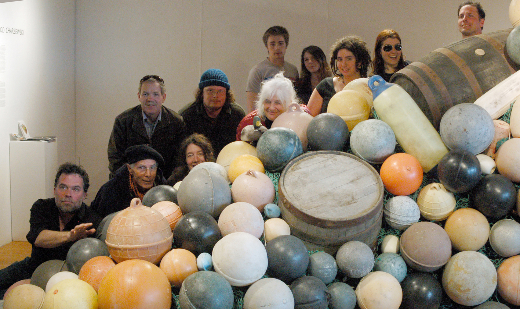 """Old Town Artist in Residence Jarod Charzewski, upper right, poses with some of the people who helped create """"Buoys and Barrels,"""" a community art project, last Friday at Bunnell Street Arts Center. From left to right are Michael Walsh, Peter Kauffman, Carl Bice, Asia Freeman, Jeremy Baugh , Wendy Erd, Darien Loftiem, Samantha Inman,  Desiree Hagen, Sarah Frary and Charzewski.-Photo by Michael Armstrong; Homer News"""