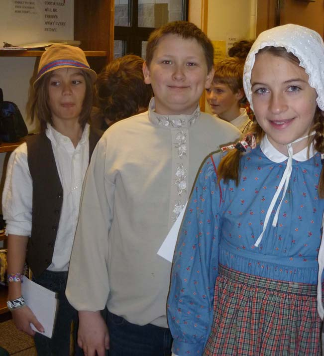 Fireweed Academy students Anthony Melkomukow, in the role of Kondraty Fefelov, a Russian mechanic; Noah Irons, as Wolfgang, a German musician; and Bea Strobel, as Victoria Gurka, a Polish seamstress, wait for a documentation as they role-play being immigrants arriving at Ellis Island during a recent lesson at Fireweed Academy.-Photo provided