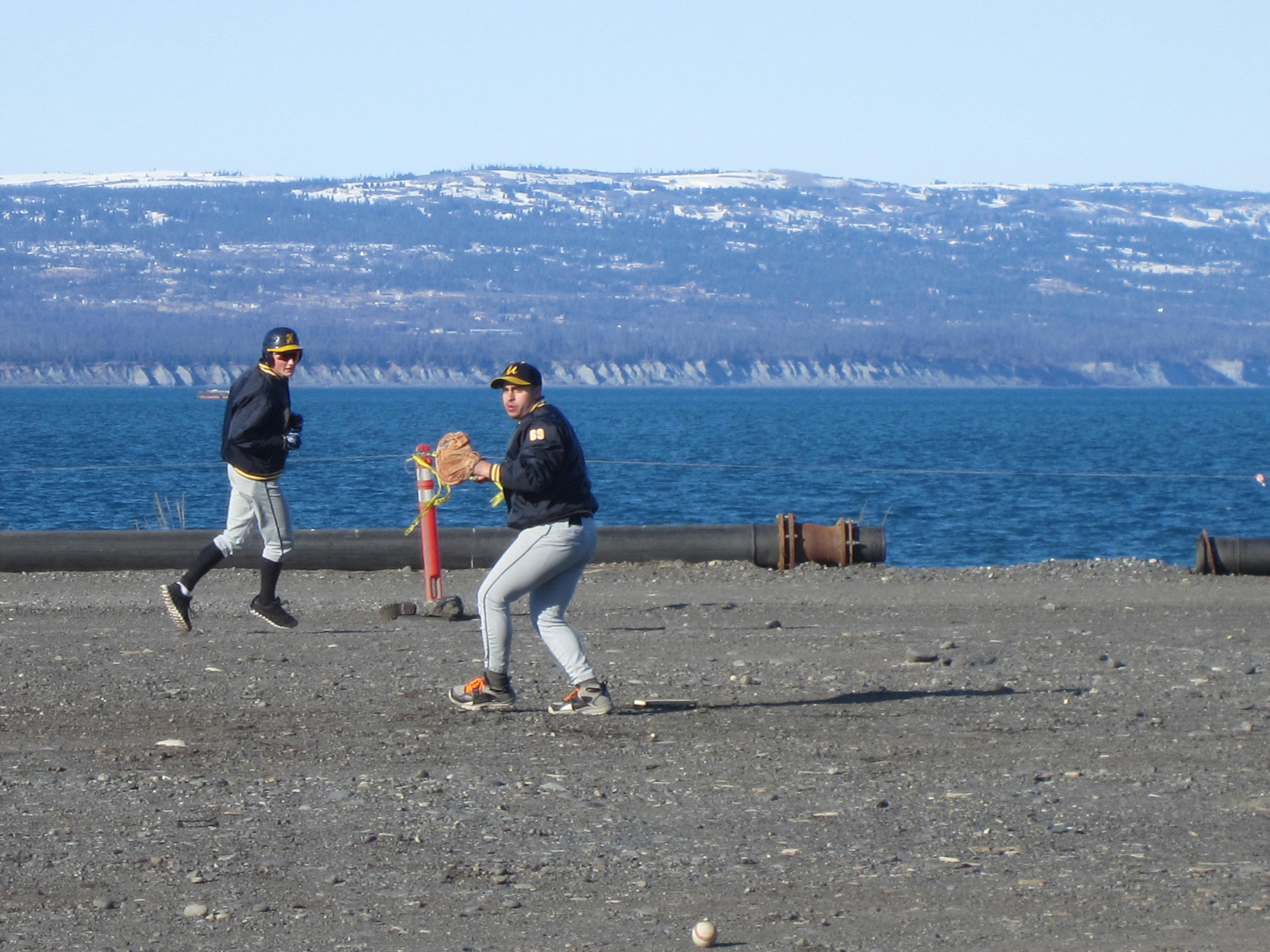 Dick Perez throws the ball during a Mariner practice on the Homer Spit, while Brian Rowe runs. The Mariners' first game of the season will be May 3 at home.