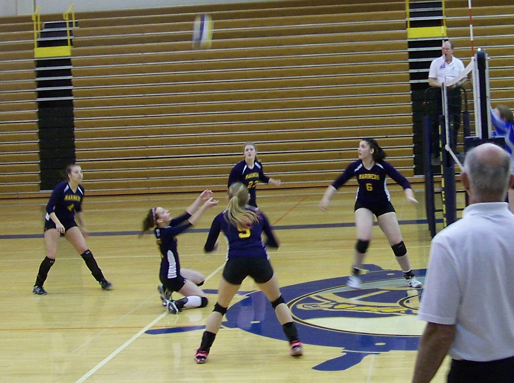The Mariner varsity volleyball team has Caroline Decreeft's back as the kneeling Decreeft sends the ball high and back across the net during Saturday's game against Cordova.-Photo by McKibben Jackinsky, Homer News
