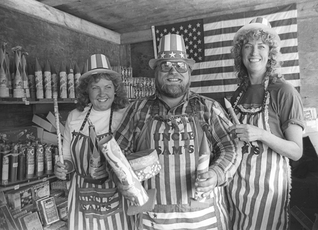 Suzanne and Mark Stevens, left, and Peggy James staff Uncle Sam's Fireworks Stand on Baycrest Hill. Fireworks were then legal to sell in Homer.-Homer News archive photo