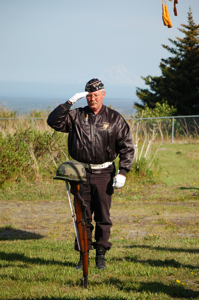 Eric Henley of the Anchor Point Veterans of Foreign Wars Auxiliary salutes a rifle and helmet symbolizing America's war dead during Memorial Day ceremonies at Hickerson Memorial Cemetery.-Photo by Michael Armstrong, Homer News