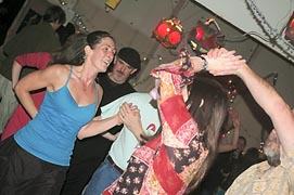 Carey Restino, left, dances at the 2012 New Year's Eve contra dance at Renn Tolman's boat shop.