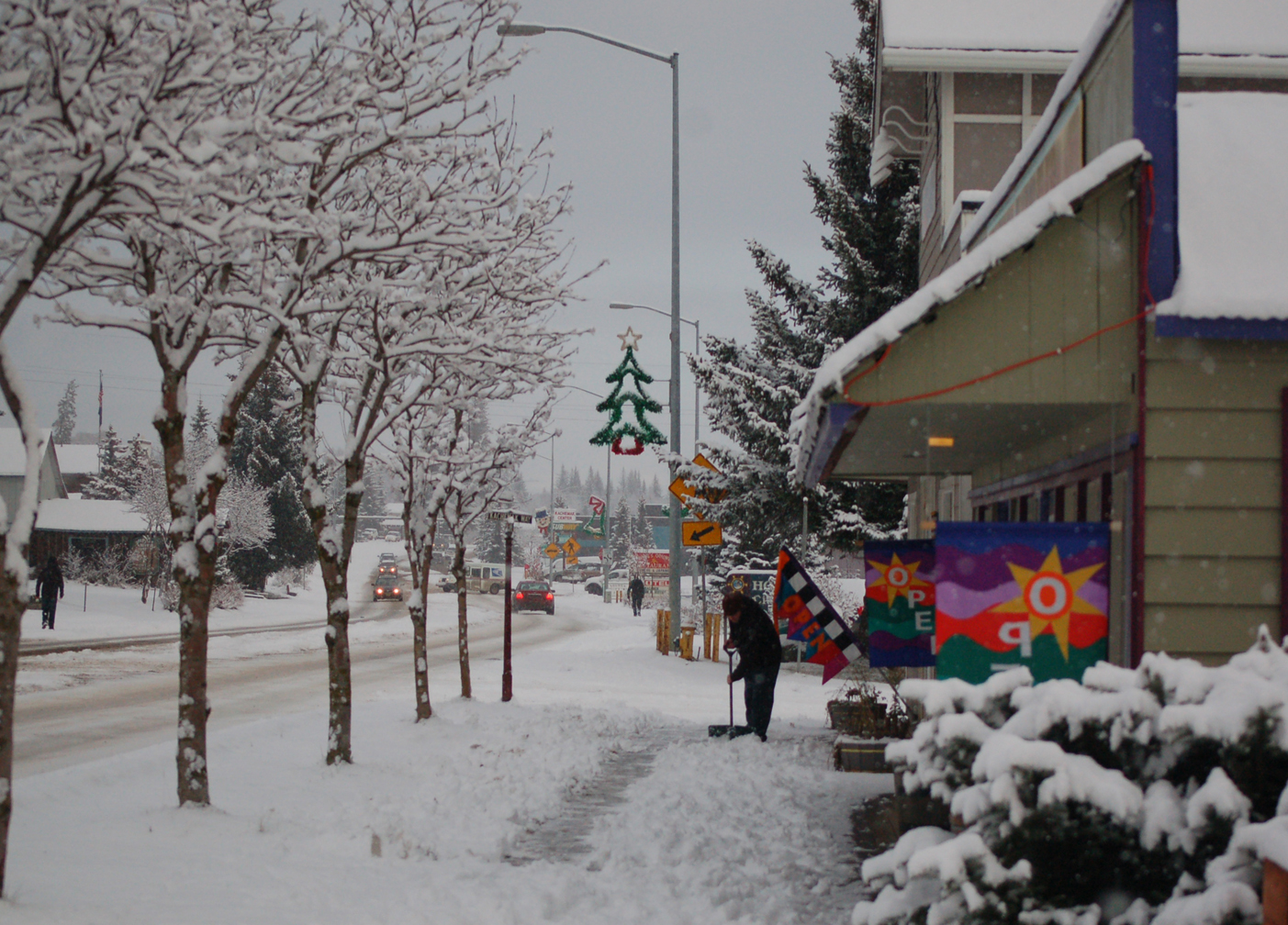 Sam Young shovels the sidewalk in front of Fireweed Gallery and Ptarmigan Arts on Monday afternoon. The weekend outlook calls for more snow on Christmas and sunshine on Friday.-Photo by Michael Armstrong, Homer News