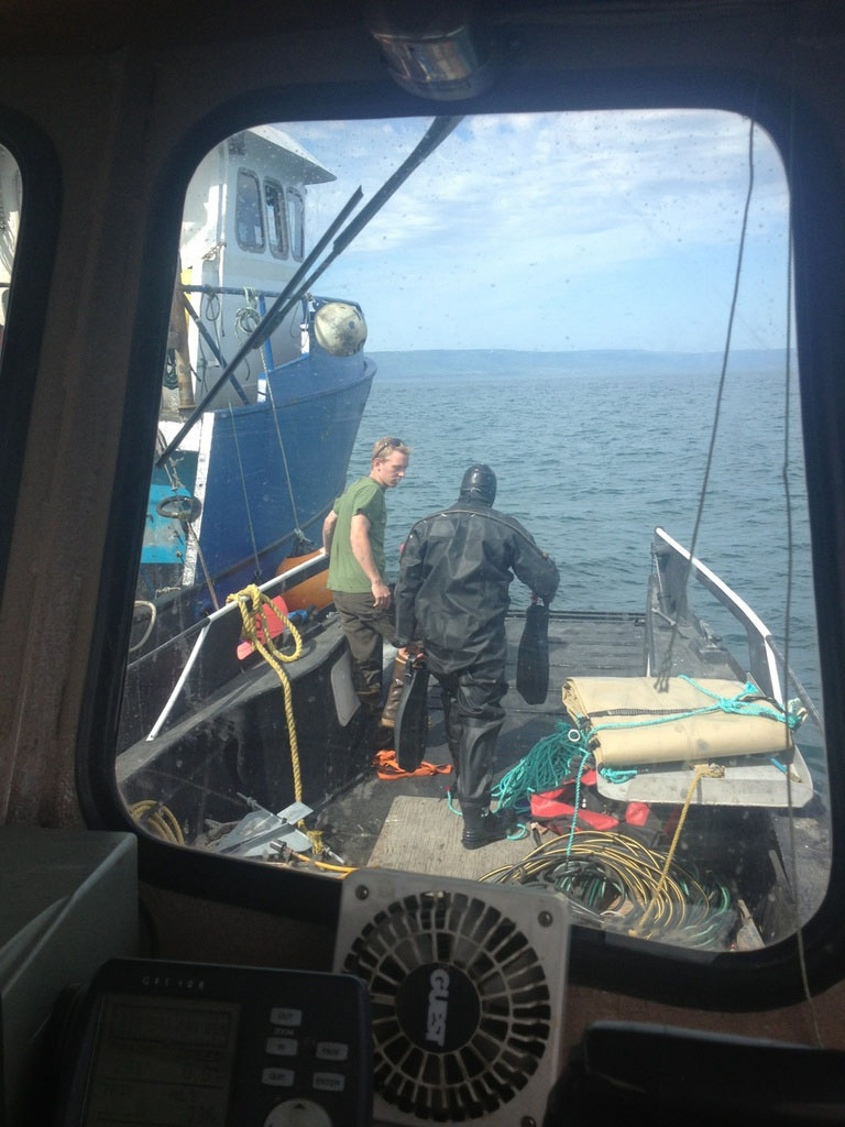 Zech Bennett, right, prepares to head into the water in an effort to right a capsized commercial fishing skiff.-Photo provided