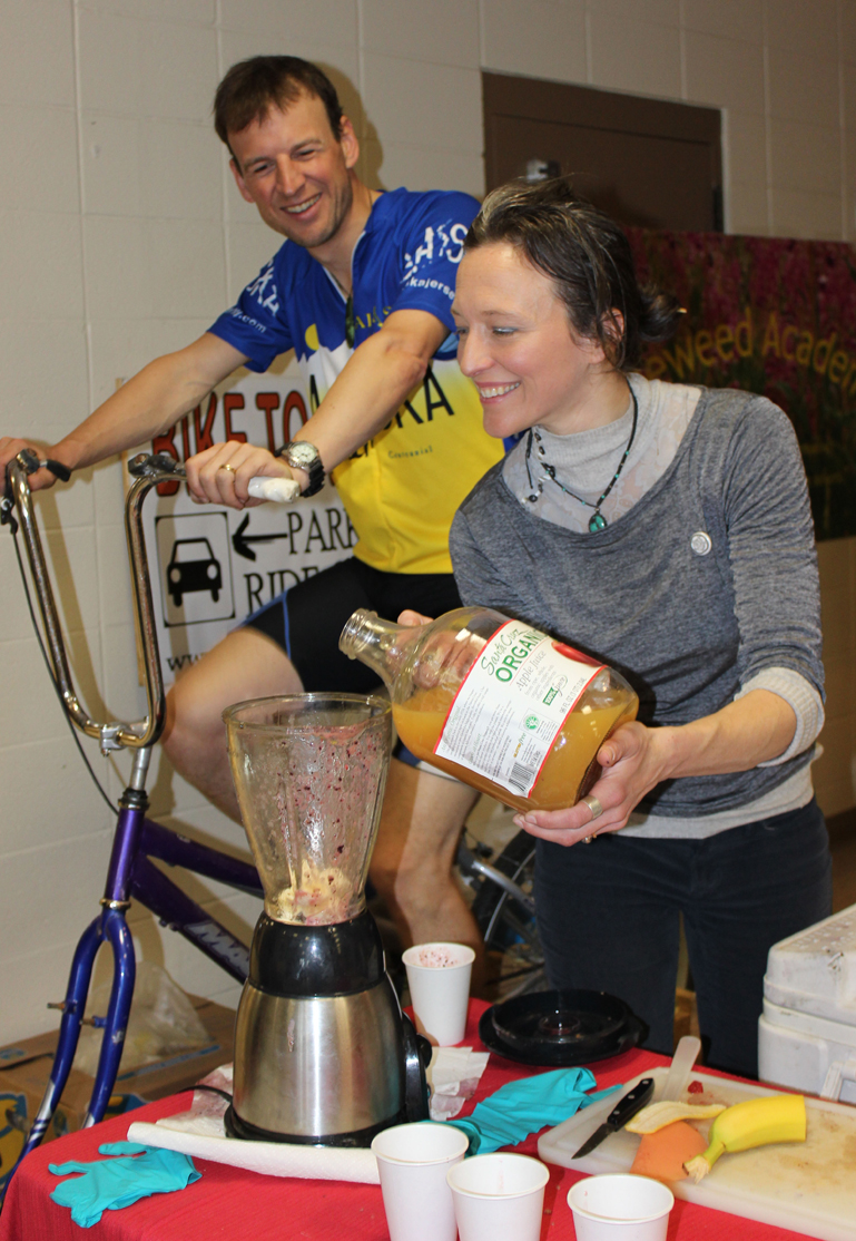 Homer Cycling Club's Martin Renner provides the energy to operate a blender and Adele Person pours the resulting smoothies for guests at Saturday's Safe Kids Fair.-Photo by McKibben Jackinsky, Homer News