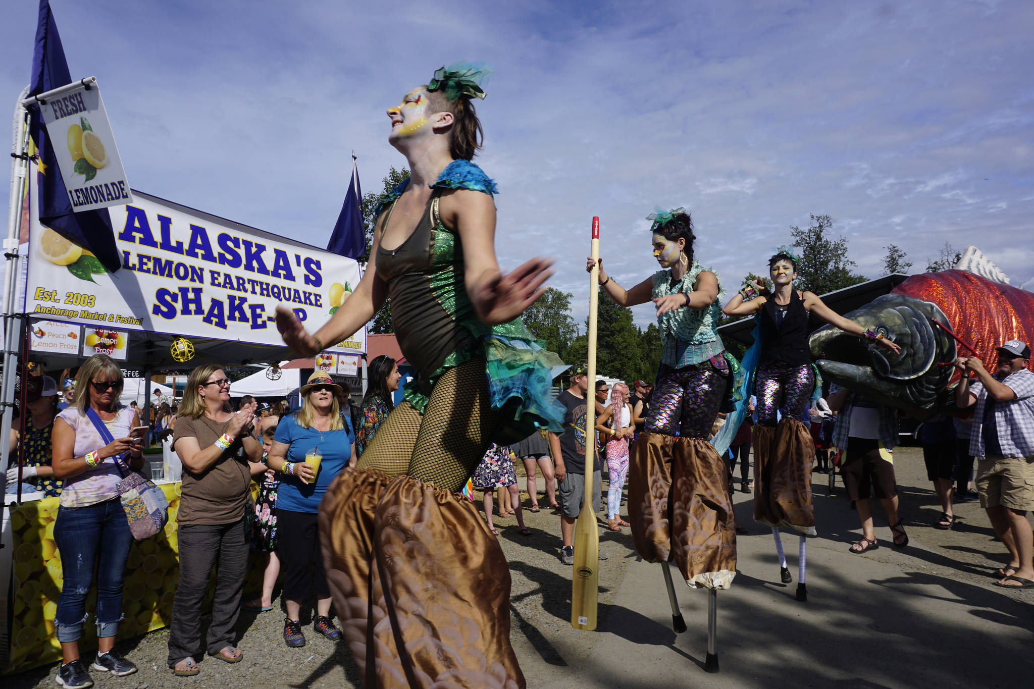 An art and music performance during Salmonfest on Saturday, Aug. 4, 2018, featured women on stilts dressed as mermaids, salmon sculptures and the LowDown Brass Band. Salmonfest attendees enjoyed warm sunny weather on Saturday at the Kenai Peninsula Fairgrounds in Ninilchik, Alaska. (Photo by Michael Armstrong/Homer News)